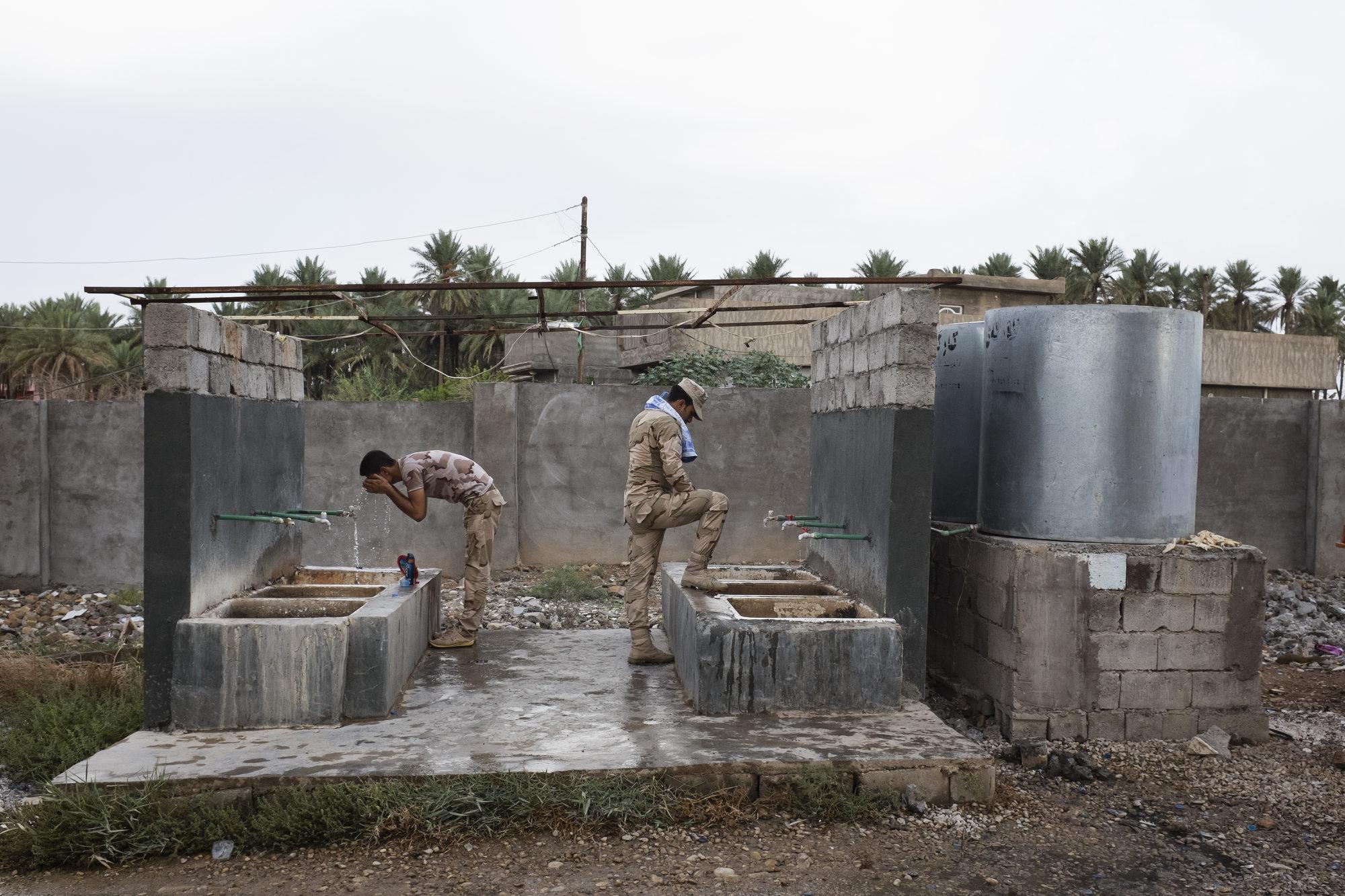 Peshmerga have a morning wash at a base.