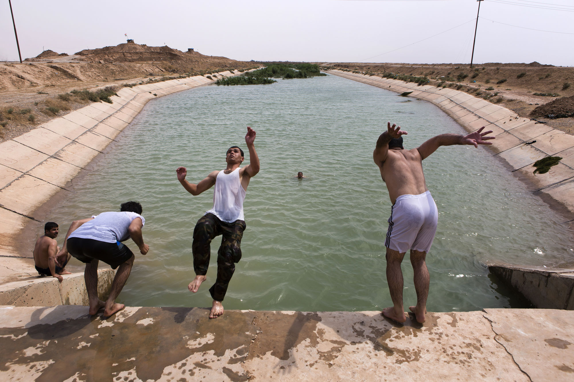 Peshmerga swim in an irrigation canal at a front line position.