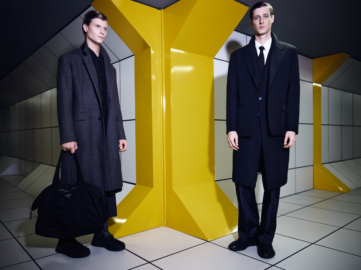 On Patrick (Left): Jacket ($2,460), Coat ($3,400), Pants ($970), Shoes (Price Upon Request), and Bag (Price Upon Request) PRADA. On Marc-André (Right): Jacket ($3,940), Coat ($4,110), Pants ($2,140), Tie ($310), Shirt (Price Upon Request), and Shoes (Price Upon Request) PRADA.