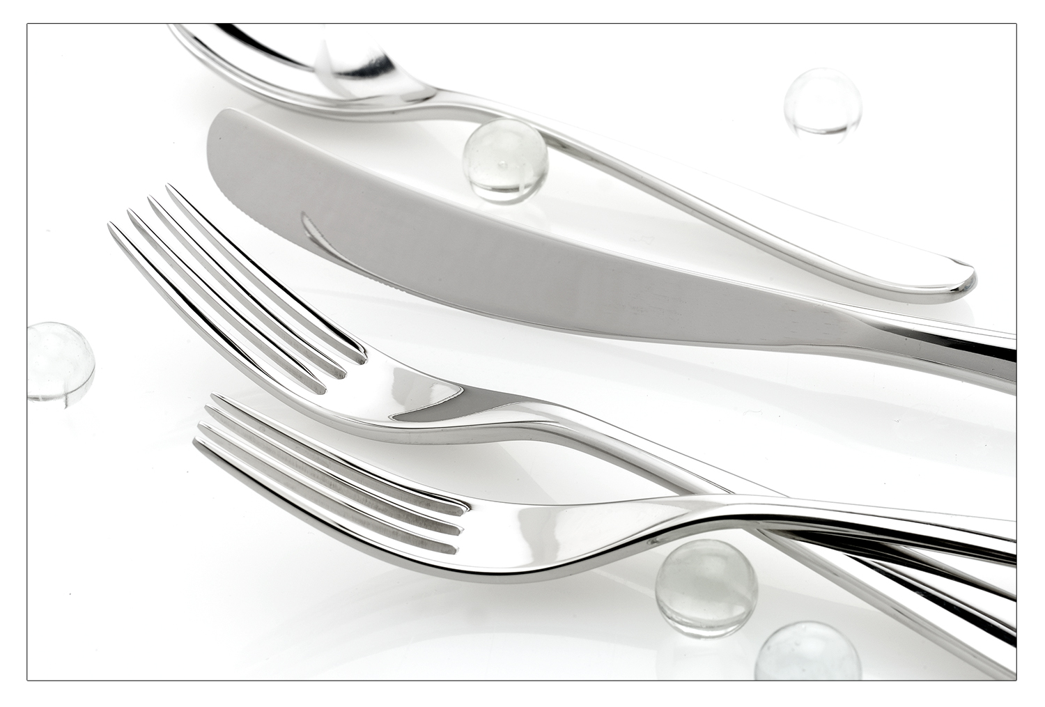 Flatware on white with clear glass marbles. Product Photo.