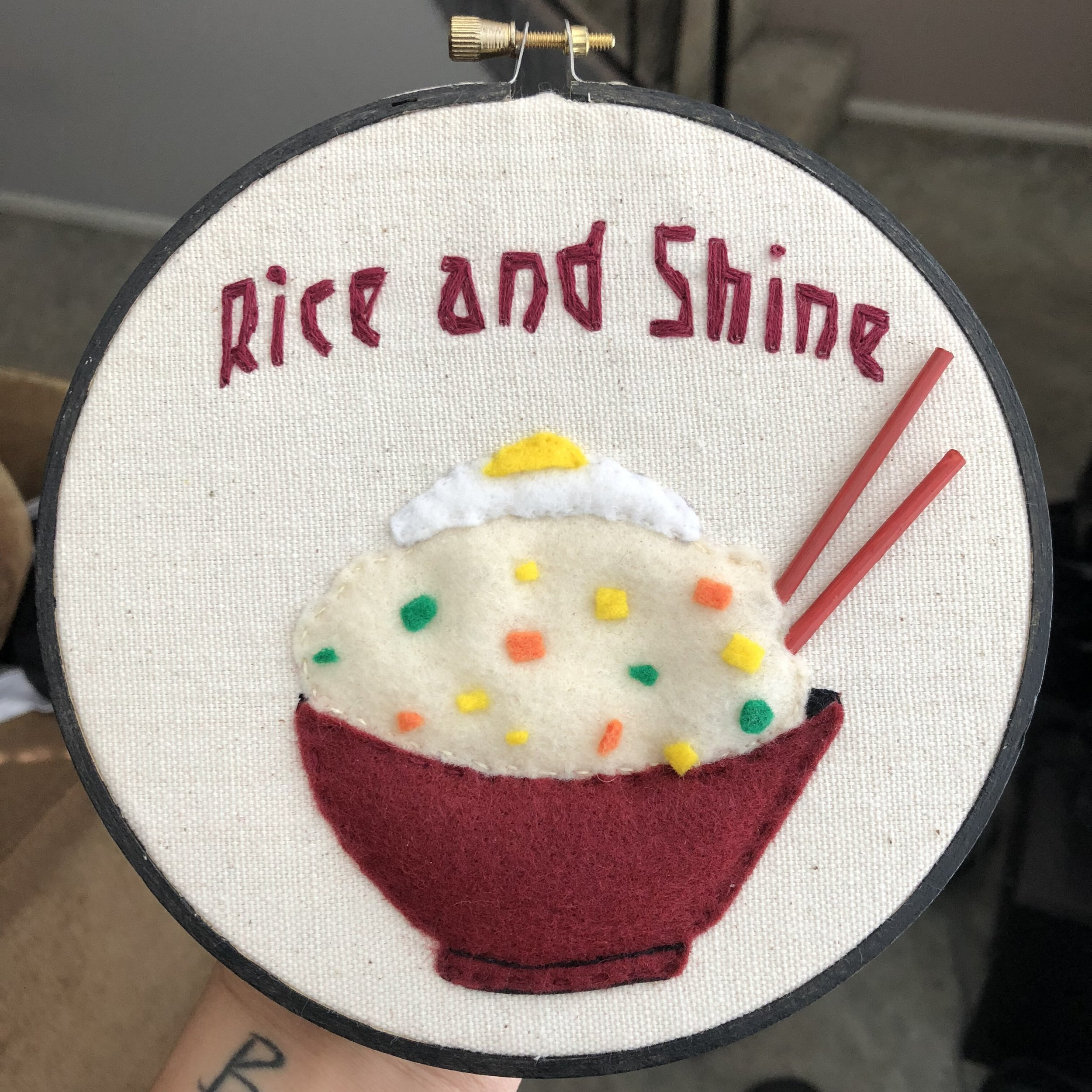 - I've never had something embroidered before. It's more than a painting cause it's got all the cool textures. I like the chopsticks and all the details that were put on the image to make it look like fried rice. The font always works out really well cause it feels like the theme matches the fried rice embroidery.