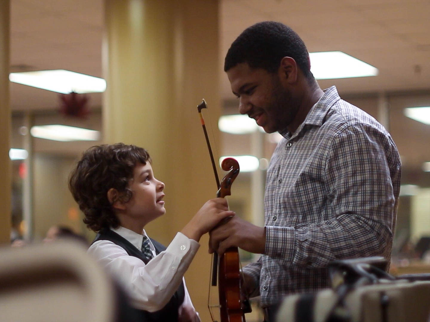 Noel helping a younger music haven student tune his violin