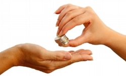 womans_hand_passing_stack_of_coins_to_another_hand.jpg