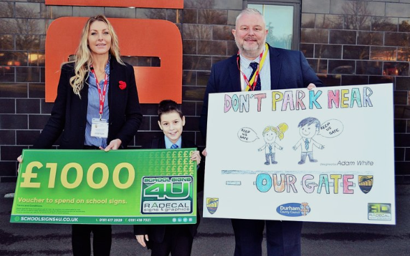 SAFER PARKING AT THE SCHOOL GATES DESIGN COMPETITION - Radecal Signs & Graphics Limited presented a £1000 voucher to spend on School signage! Congratulations to Adam White of Dene Community School for winning the first prize in the Road Safety Design Competition, ran by Durham County Council's Road Safety Manager, Paul Watson, and Road Safety Officer, Alison Lonsdale!(Left to right) Radecal Signs & Graphics Project Manager, Serena Wallace, Year 7 Student, Adam White, Durham County Council Road Safety Manager - Paul Watson.