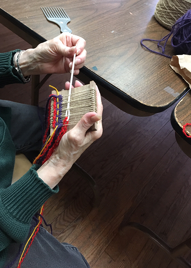 student weaving on palm-sized tapestry loom at the NCJWNY Council Lifetime Learning Center weaving studio, 2018