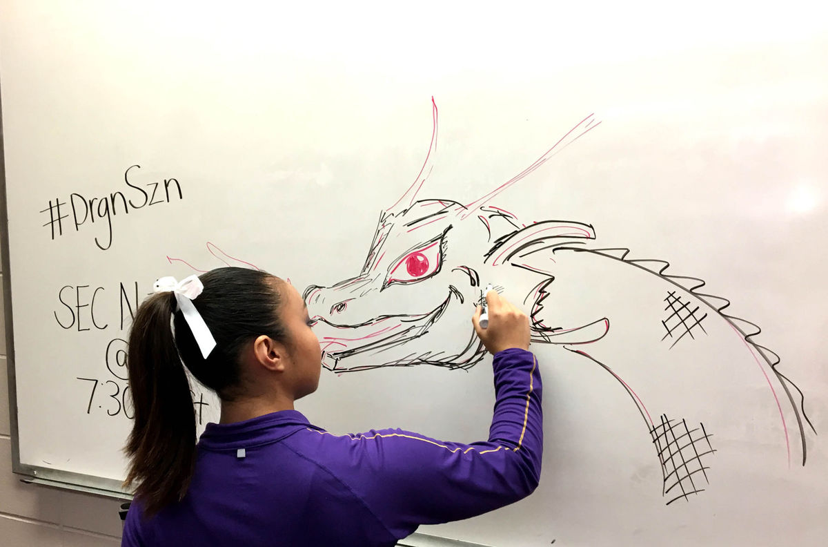 LSU gymnast Erin Macadaeg draws a fire breathing dragon on a whiteboard in the team locker room earlier this season.