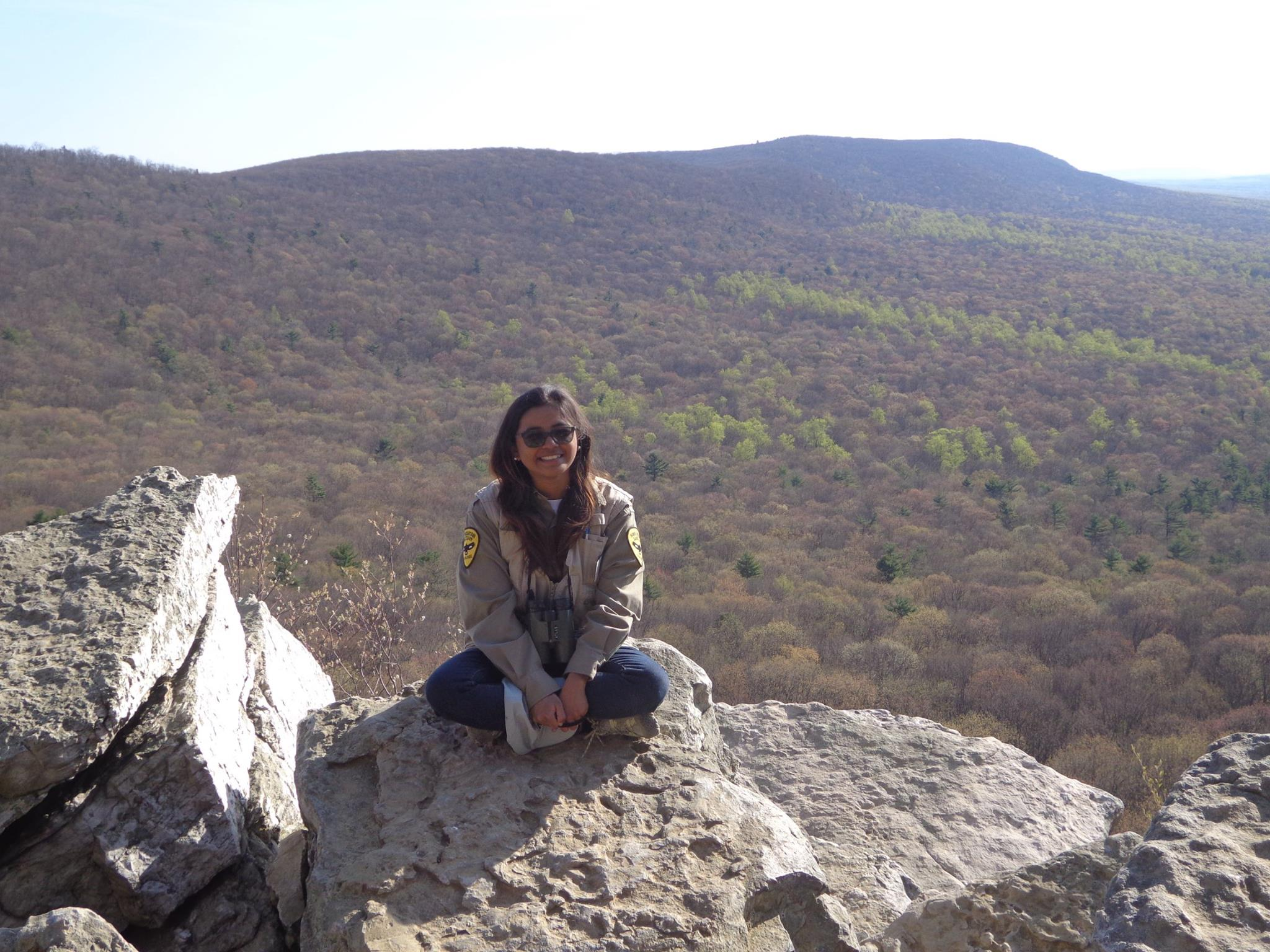 Pat sitting atop boulders at South Lookout during her traineeship in 2016.