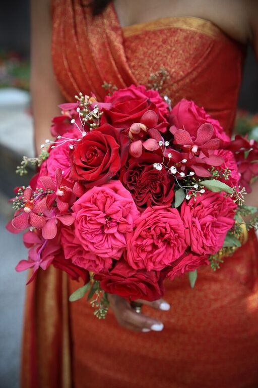 The Bridal Bouquet features red garden roses, hot pink garden roses, seeded eucalyptus, red mokara orchids and crystal beaded accents.