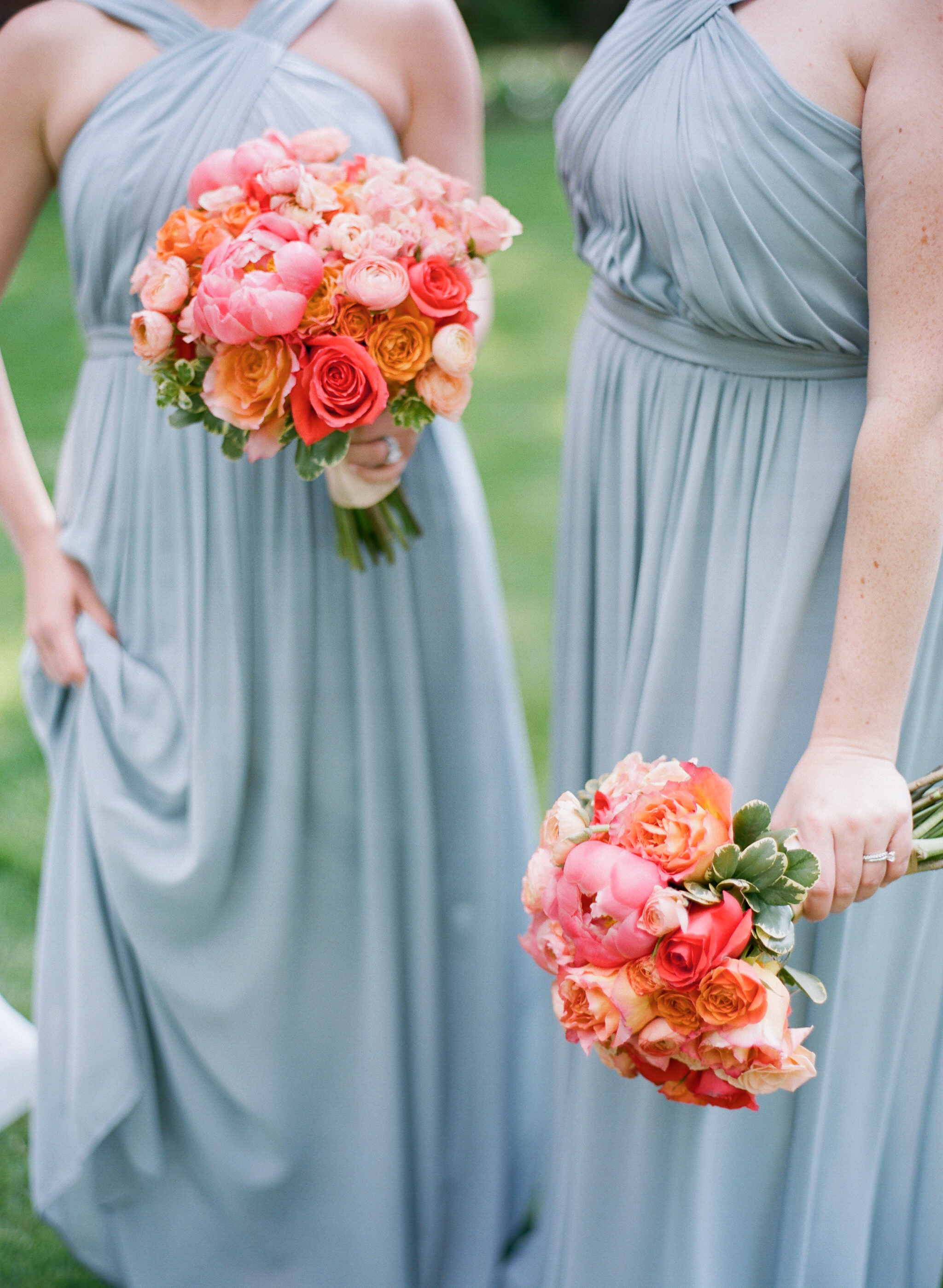 These stunning bridesmaids bouquets feature coral peony, oranges roses, pink ranunculus and soft spray roses.
