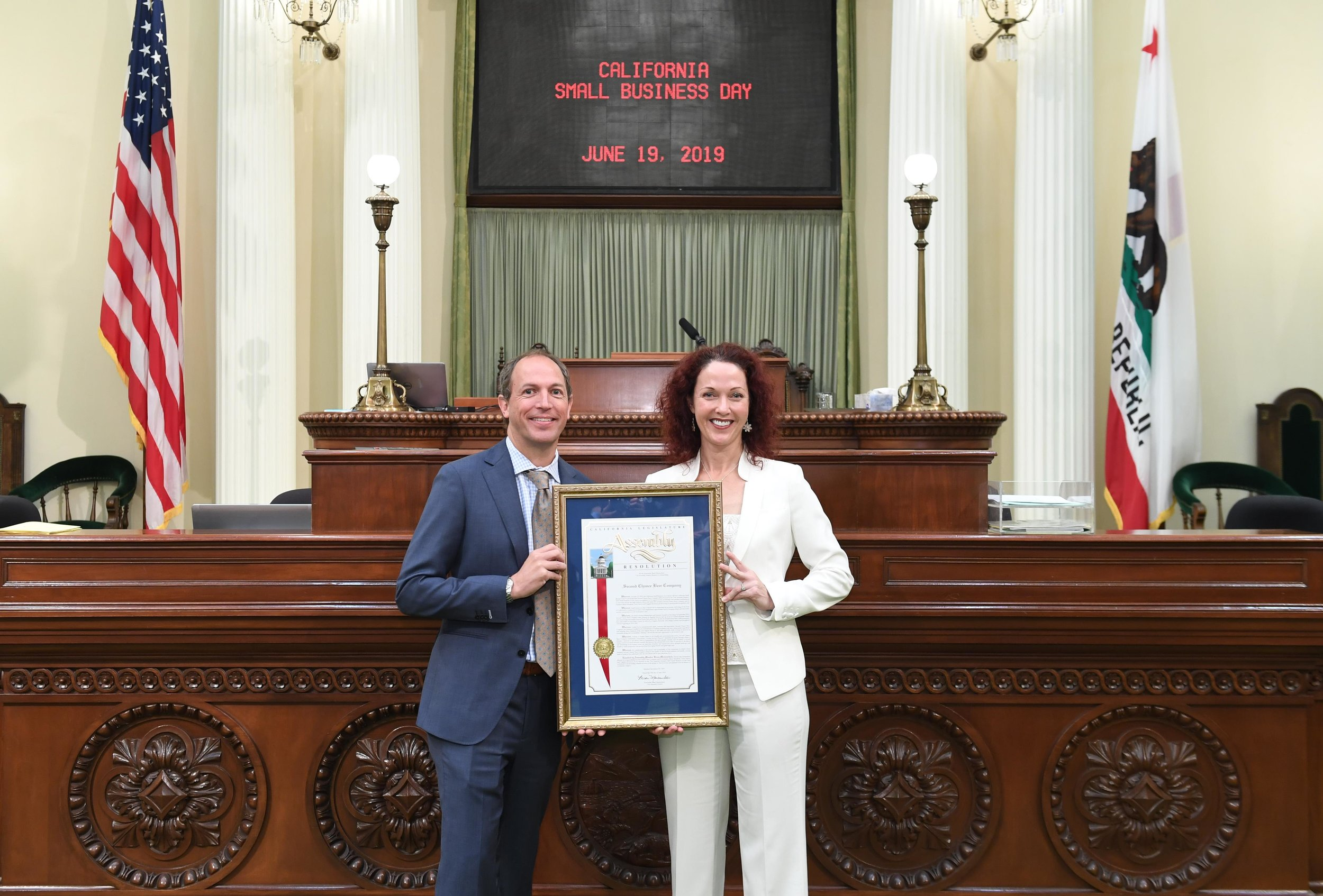 Assemblymember Brian Maienschein presents co-owner Virginia Morrison with a plaque recognizing Second Chance Beer Co. as the 2019 Small Business of the Year for the 77th California Assembly District.