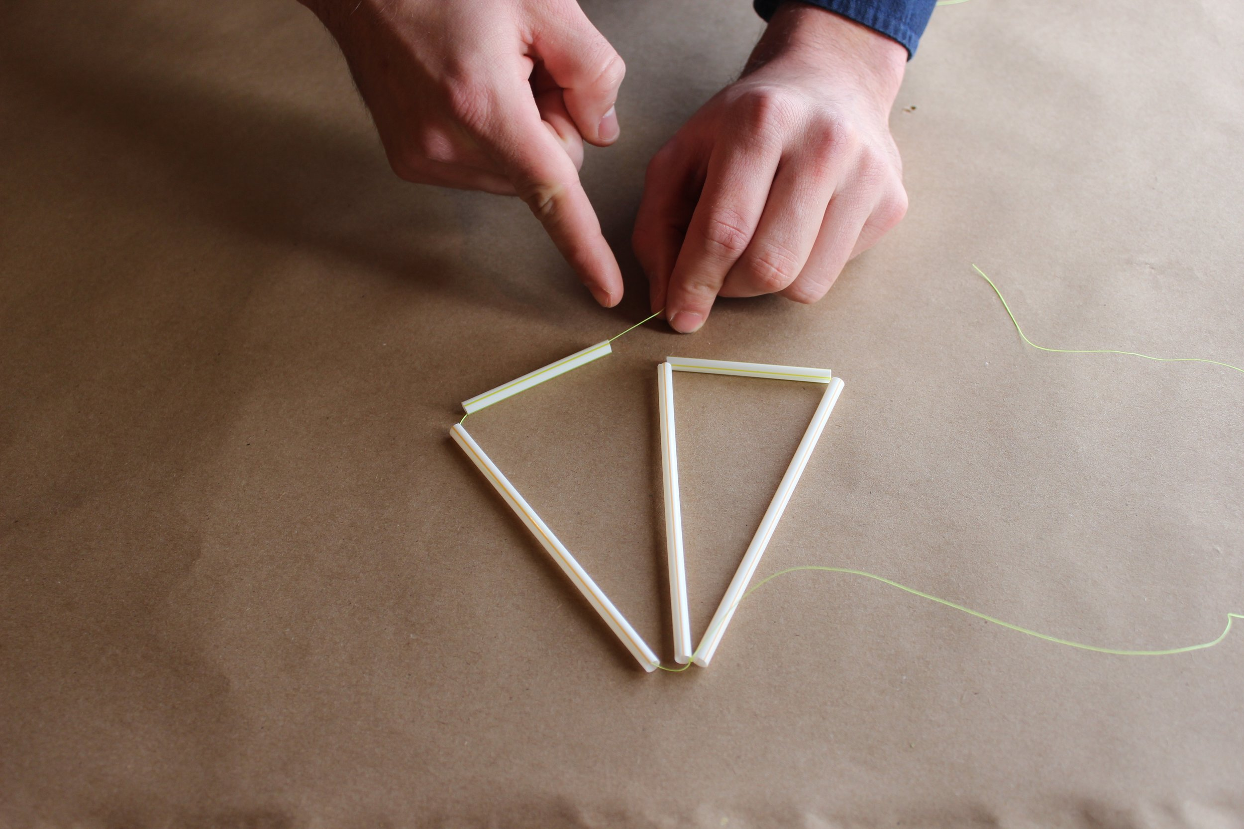 Step 4.) Thread the piece on your right through a 2.5 inch straw to form a triangle and tie it tightly at the bottom.