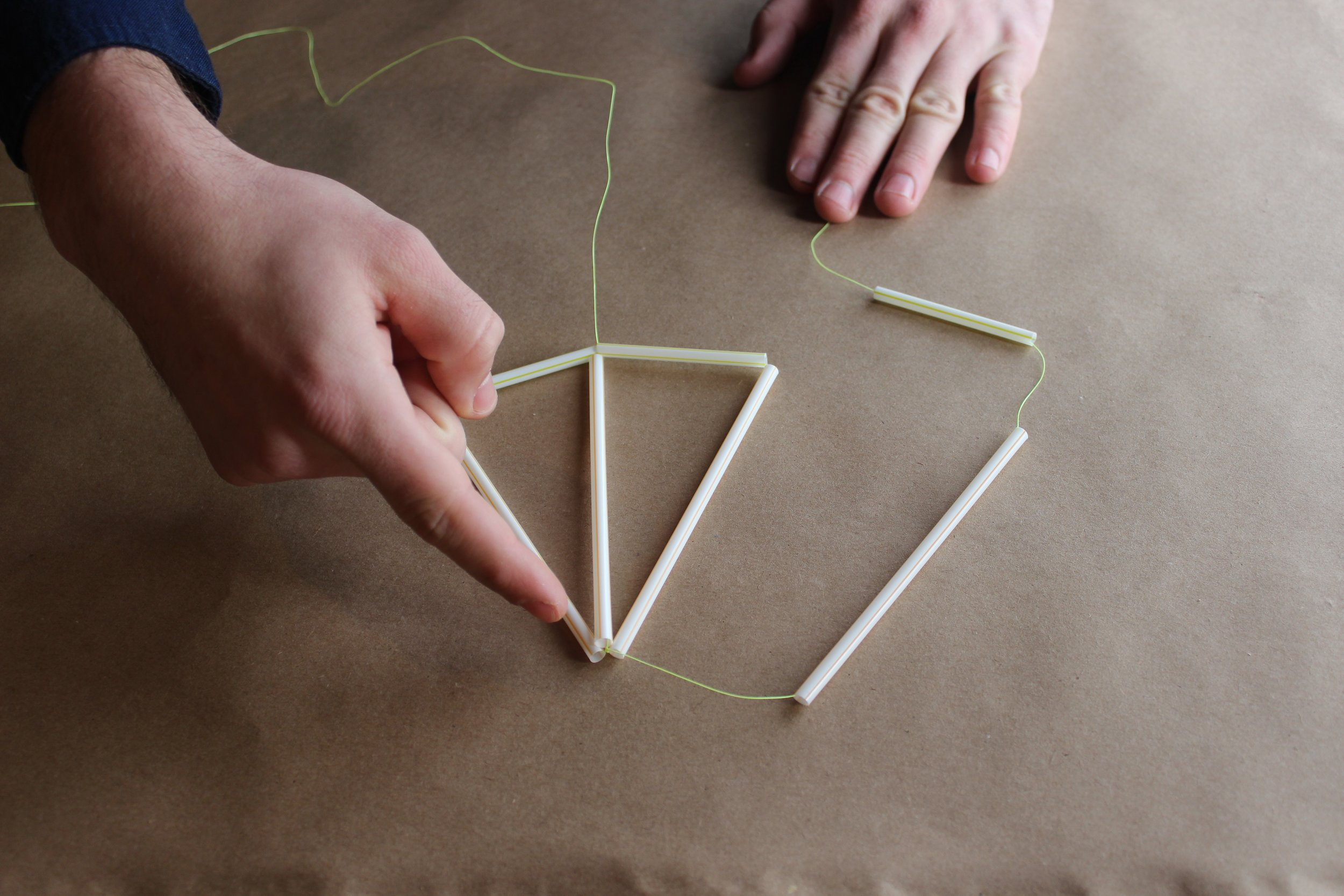 Step 5.) Using the string coming out of the top, connect it to another 5 inch piece then another 2.5 inch piece. Connect them to create your third triangle and tie it off at the bottom.