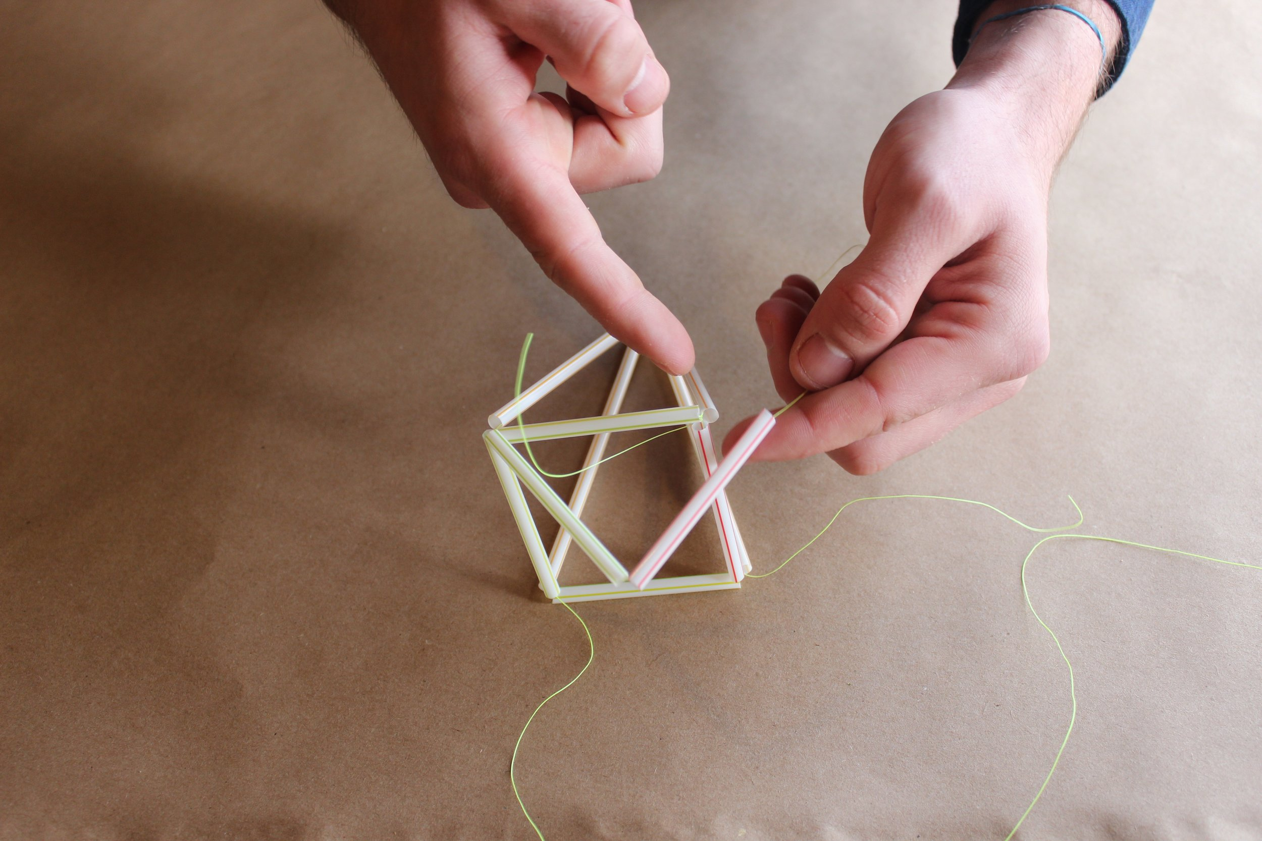 Step 8.) Now you should have (4) pieces of string coming off the base of the square. Take (1) of these strings along with (2) 2.5 inch pieces of straw and thread them on the same string. Attach the string to the opposite corner creating a triangle.