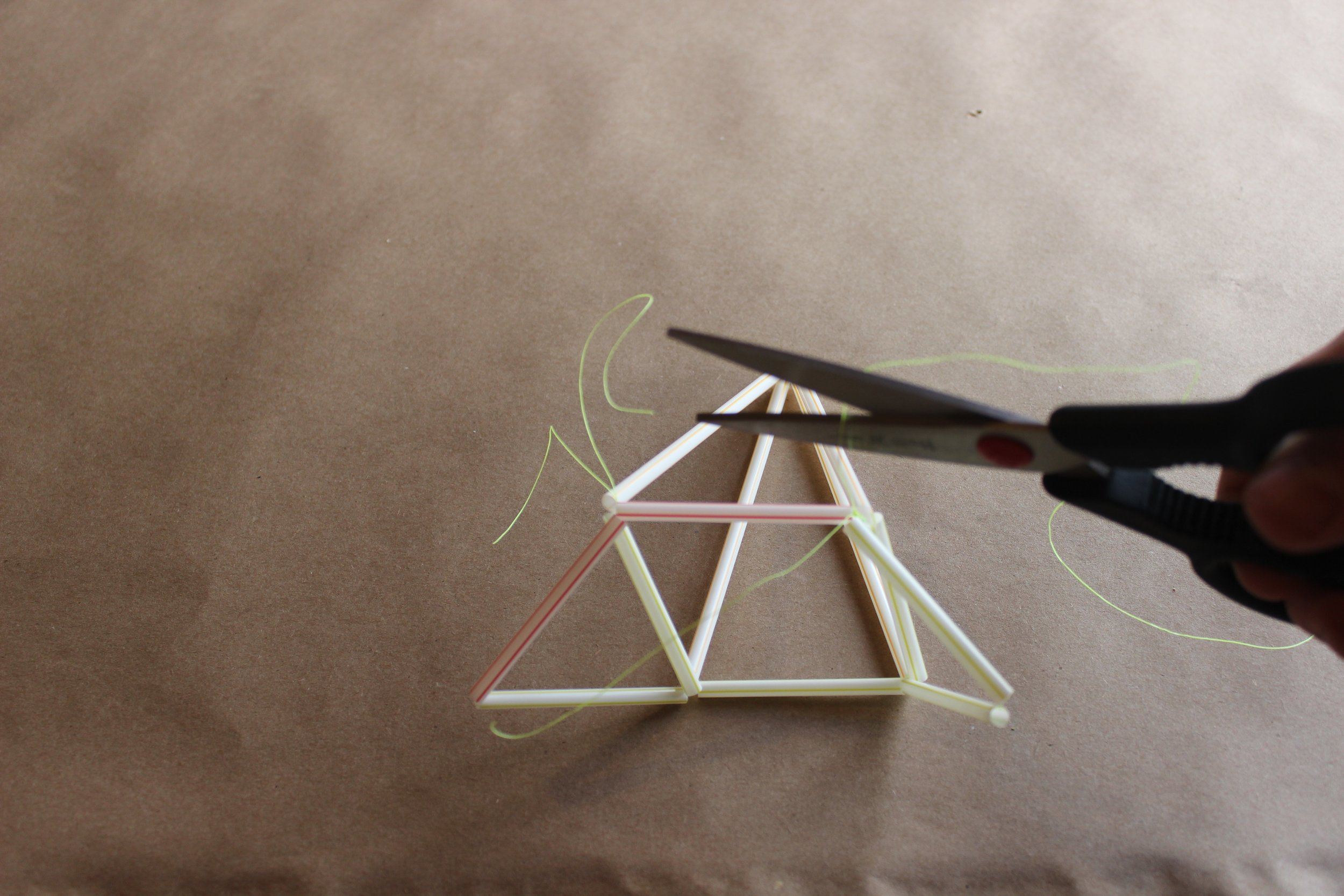 Step 10.) Cut off the excess string from all of the connections. Tie the two bottom triangles together with another piece of string.