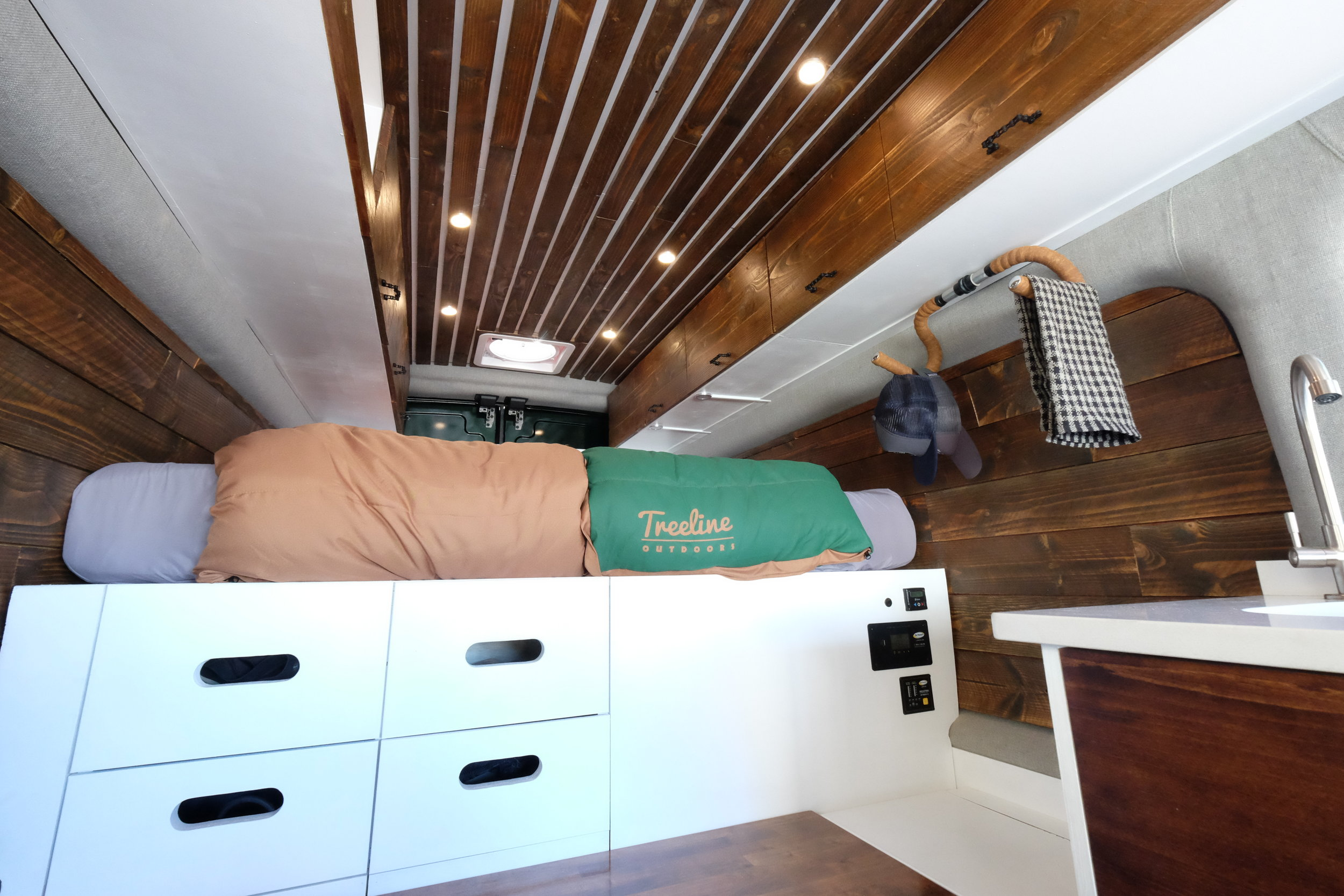 Dan wanted a cabin like space that was not only handsome, but also includes all of the amenities for life on the road. His Transit is packed with storage from under-bed shelving to upper cabinets that run the full length of the van's interior.