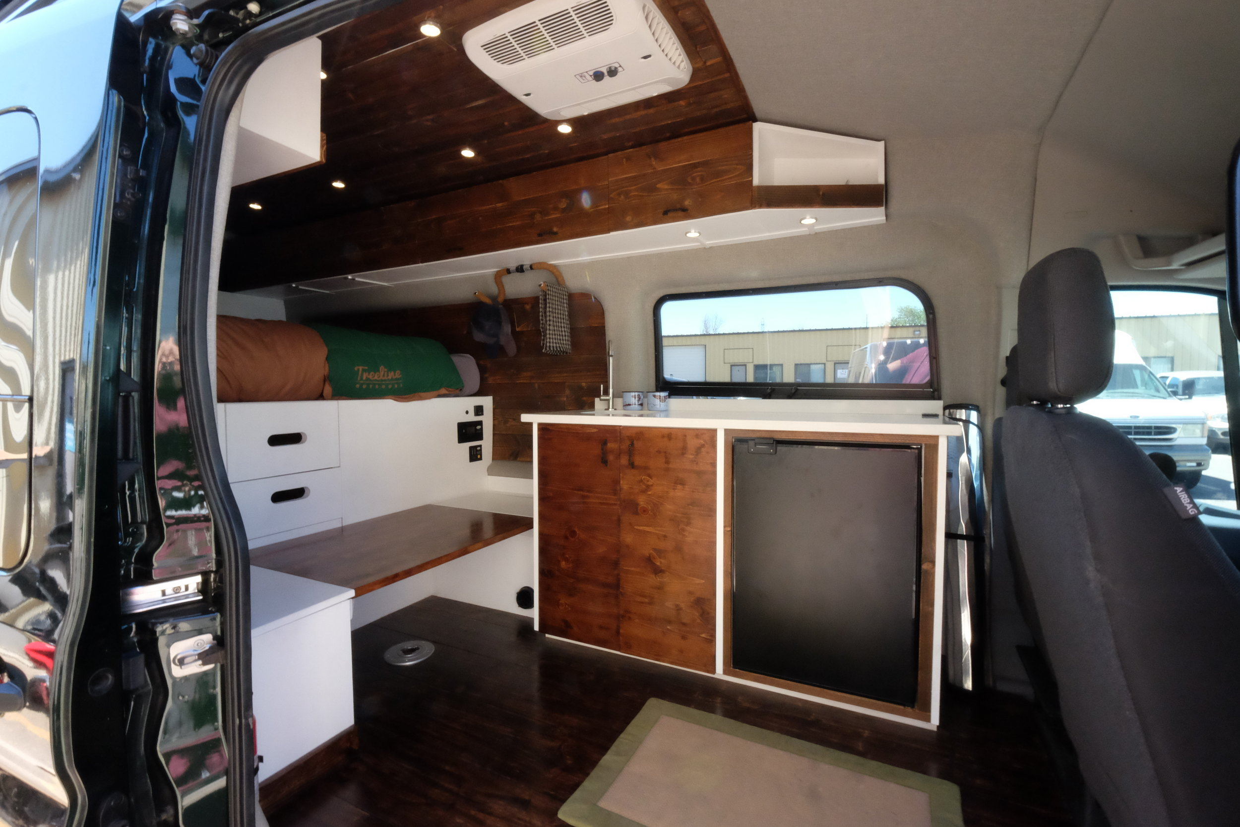 A Coleman Mach 8 AC is run off of a shore power plug and keeps Dan's van and dog cool on hot days. A 4 cu. ft. Truckfridge keeps the after-run beer cold, and the bench doubles as a table for two using a removable pedestal mount.