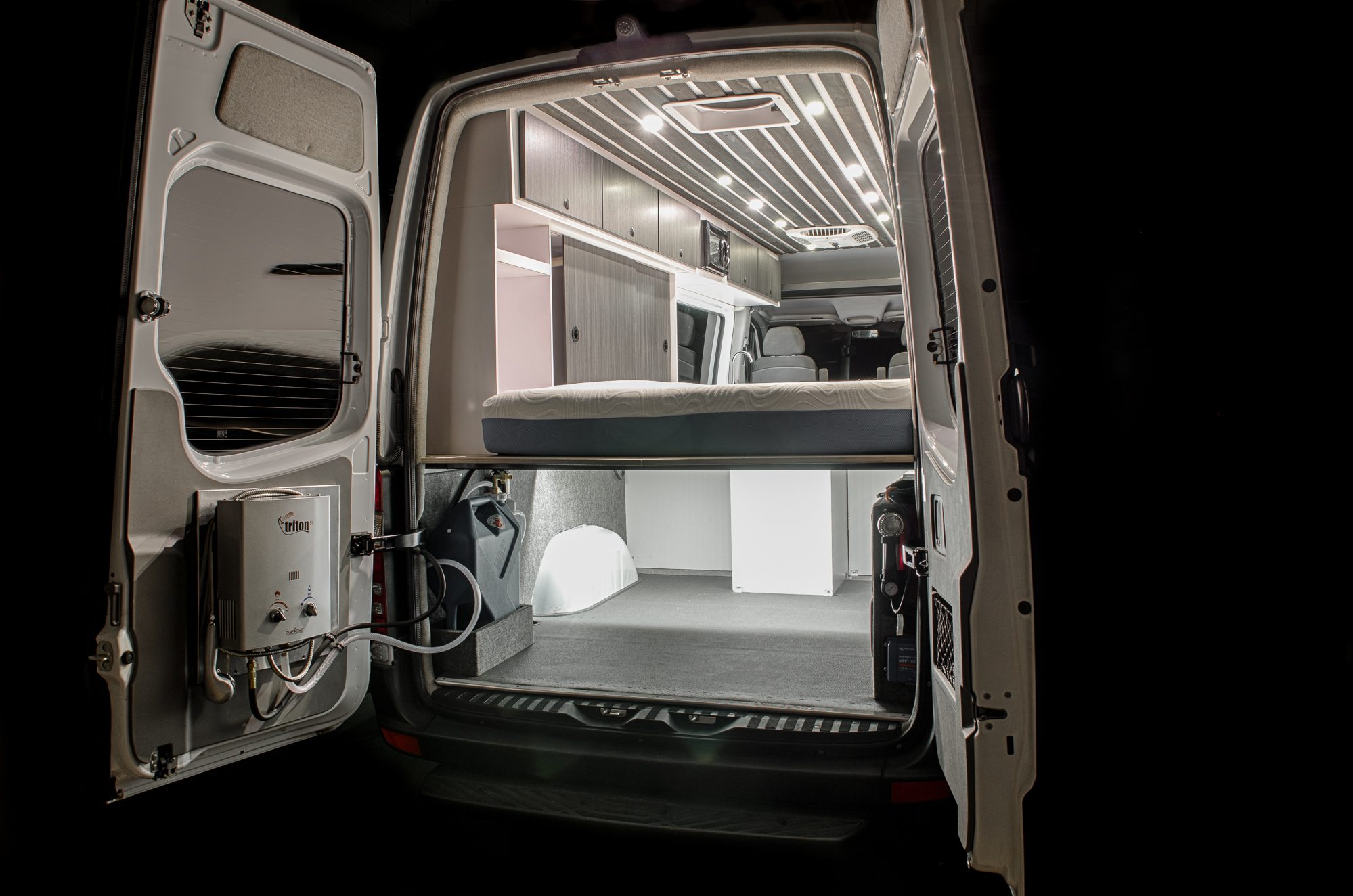 This build incorporates a custom stained slatted ceiling, one off CNC cut cabinetry, and 2-zone (dimmable) LED lighting to highlight it all. Mounted to the rear door is a Camp Chef propane heated shower system fed by a 7-gallon jerry can and electric water pump. 500W of solar feeds 5 Battleborn lithium batteries to power everything from the Remote Direct TV system, Coleman Mach 8 A/C unit, air compressor, Isotherm refrigerator, and Kicker subwoofer.