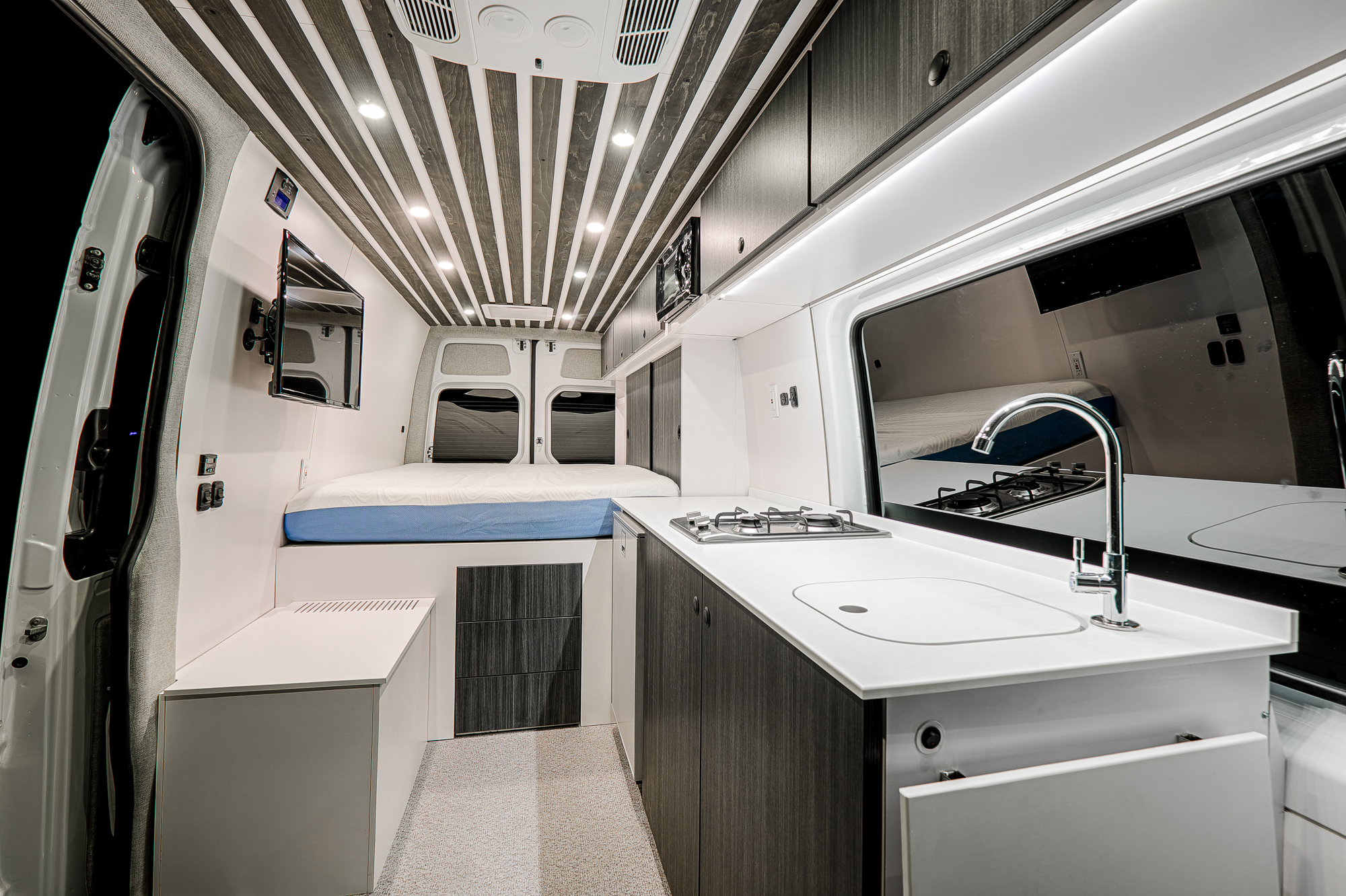 A Summit range and stainless steel sink sit inside of a CNC cut Corian countertop. A stainless steel Isotherm fridge is coupled with an additional freezer unit hidden inside of the box/bench/seat shown on the left. A wall-mounted LED TV along with flush-mounted Pushloc drawers under the bed supply extra style and comfort while on the road for long weekends.