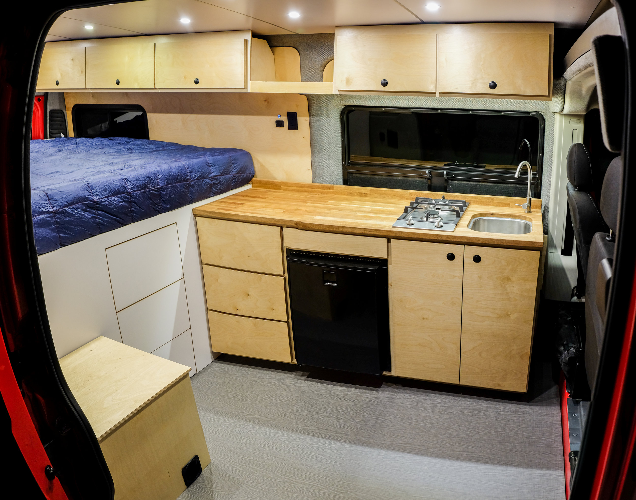 """Rob approached us to build his perfect adventure van - a 159"""" Extended Promaster. The custom CNC cut formica walls and ceiling ensure that this sleek interior will withstand every type of climate and bumpy road. 320W of Go Power solar feeds 3 Battleborn lithium batteries to fuel a 4-zone dimmable LED lighting system, Isotherm refrigerator, remote controlled Maxxair fan, and all of Rob's personal gadgets."""