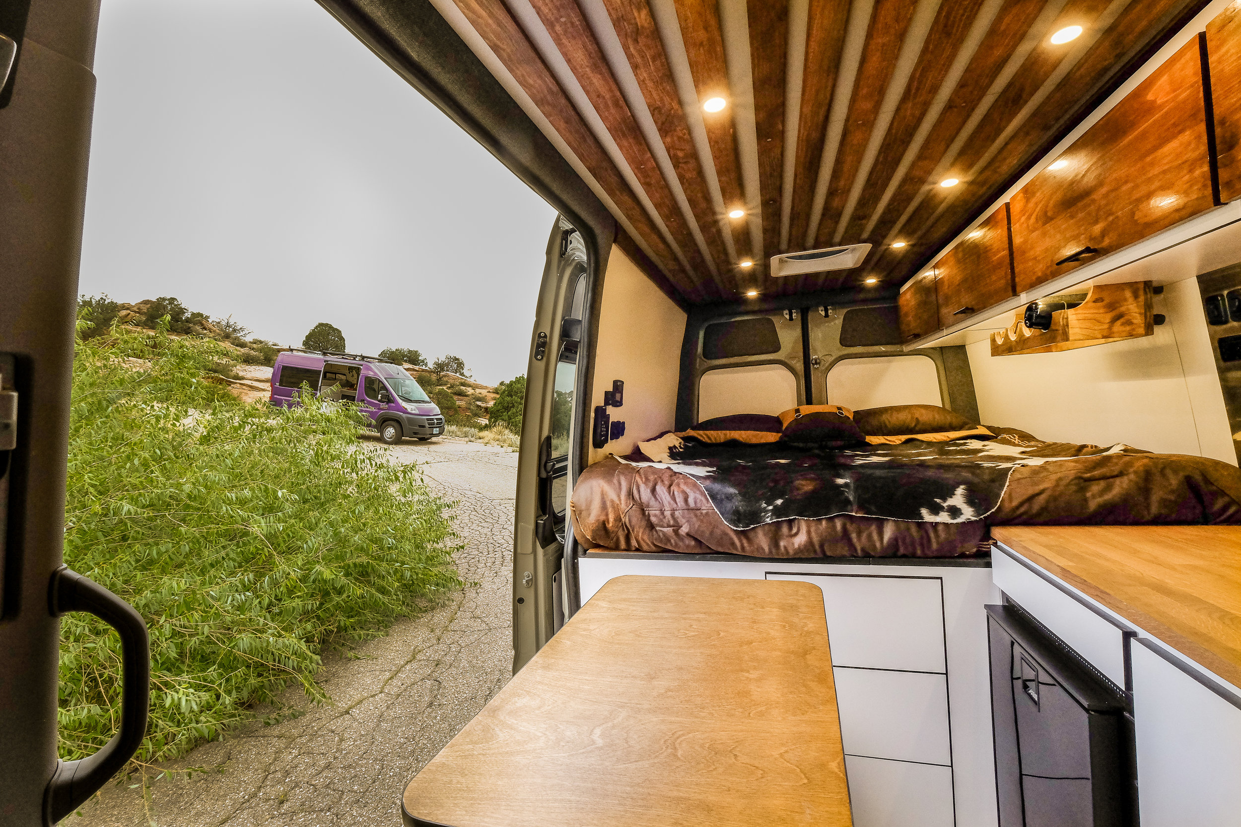 "This Mercedes Sprinter 4x4 conversion features enough room for a queen size 6"" memory foam mattress and a touch-to-open 3 drawer unit for under the bed storage."