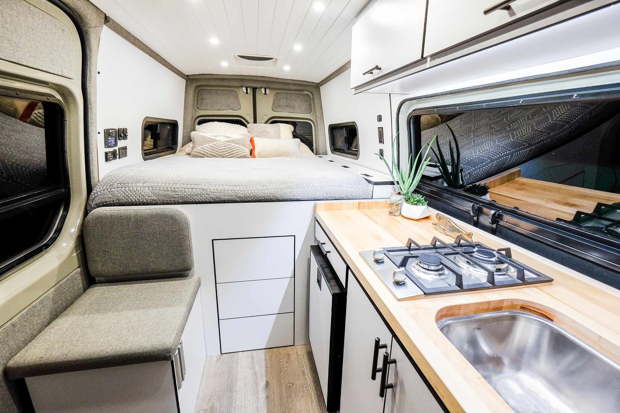 This Sprinter's sleek and modern design is chalked full of custom details. From the tongue and groove ceiling, to the bedside storage unit, custom fabricated pull-up bar, water filtration system, standing desk and pergola floor; JOMOVAN is one of the cleanest builds that has ever left the Vanlife Customs shop.