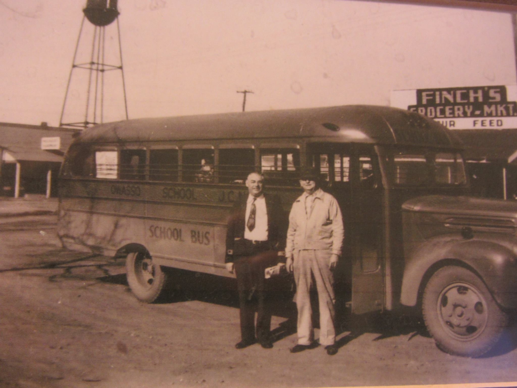 Early Owasso School Bus, Mr. Pinkerton, Superindent 1945-48, and Mr. Lewis Finch grocery owner. Finches Grocery was on East Broadway, Mounger Hardware is in the background on Main St. with the first water tower standing proud.