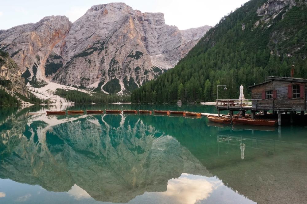 curio.trips.italy.dolomites.lake.sunset.boats.hut.landscape.jpg