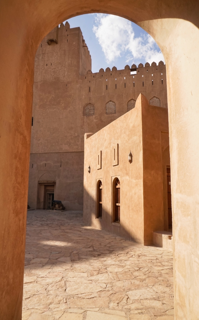curio.trips.oman.nizwa.castle.exterior.arch.light.portrait.jpg