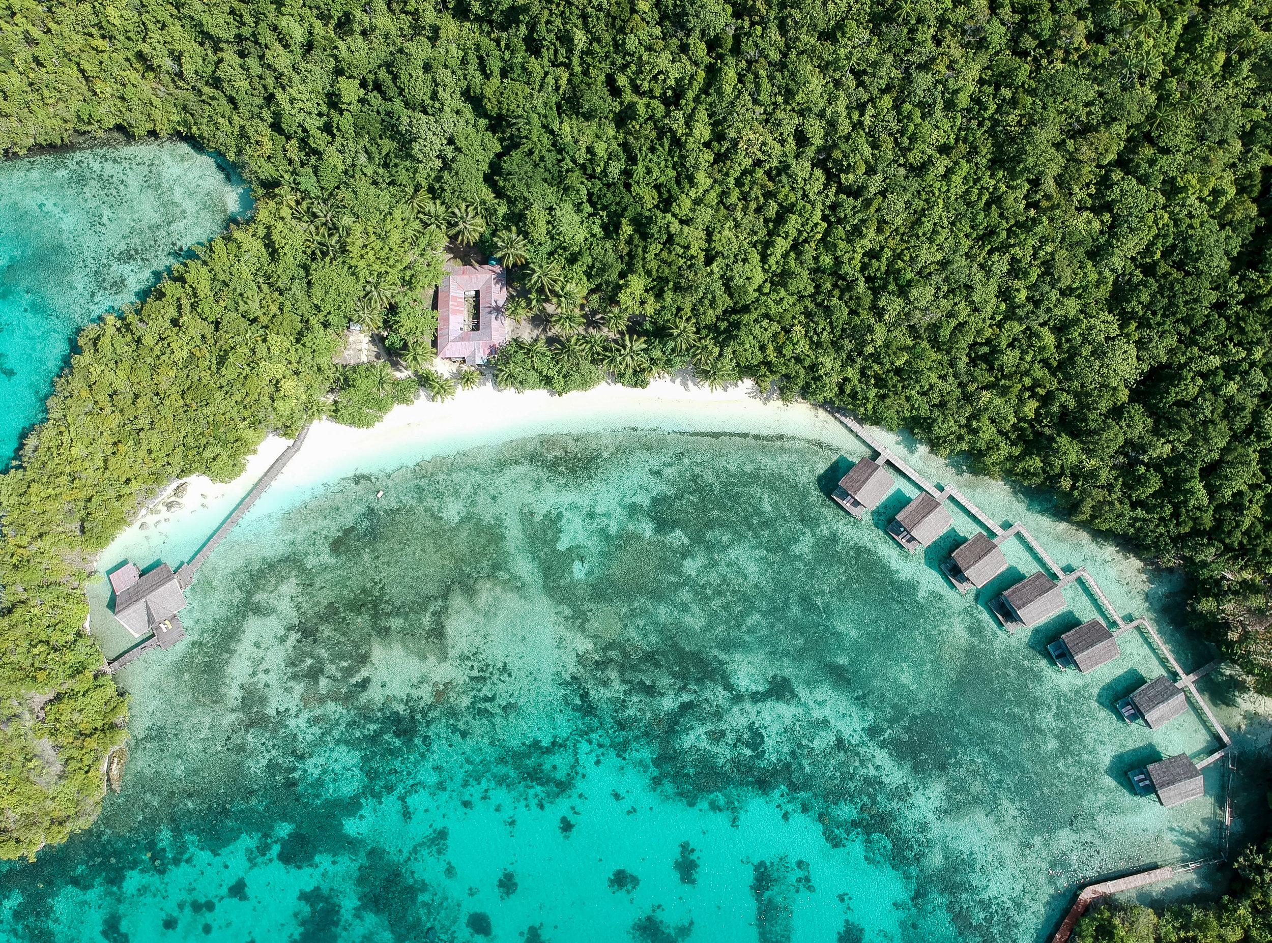 curio.trips.indonesia.raja.ampat.private.island.overwater.villas.beach.drone-2.jpg