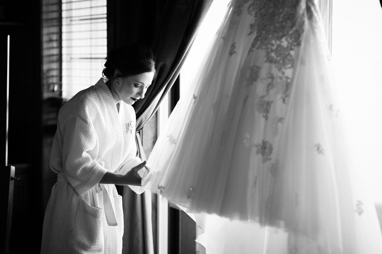 Bride looks at wedding dress on wedding day.