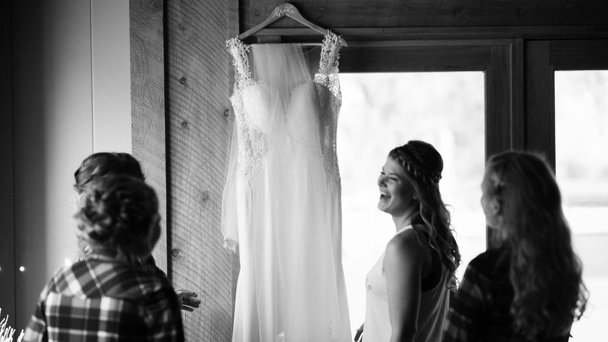 Wedding dress hangs on door bride laughs in foreground.