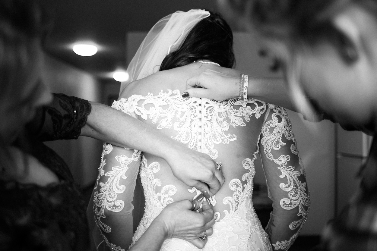 Wedding photojournalism, bride getting into dress.