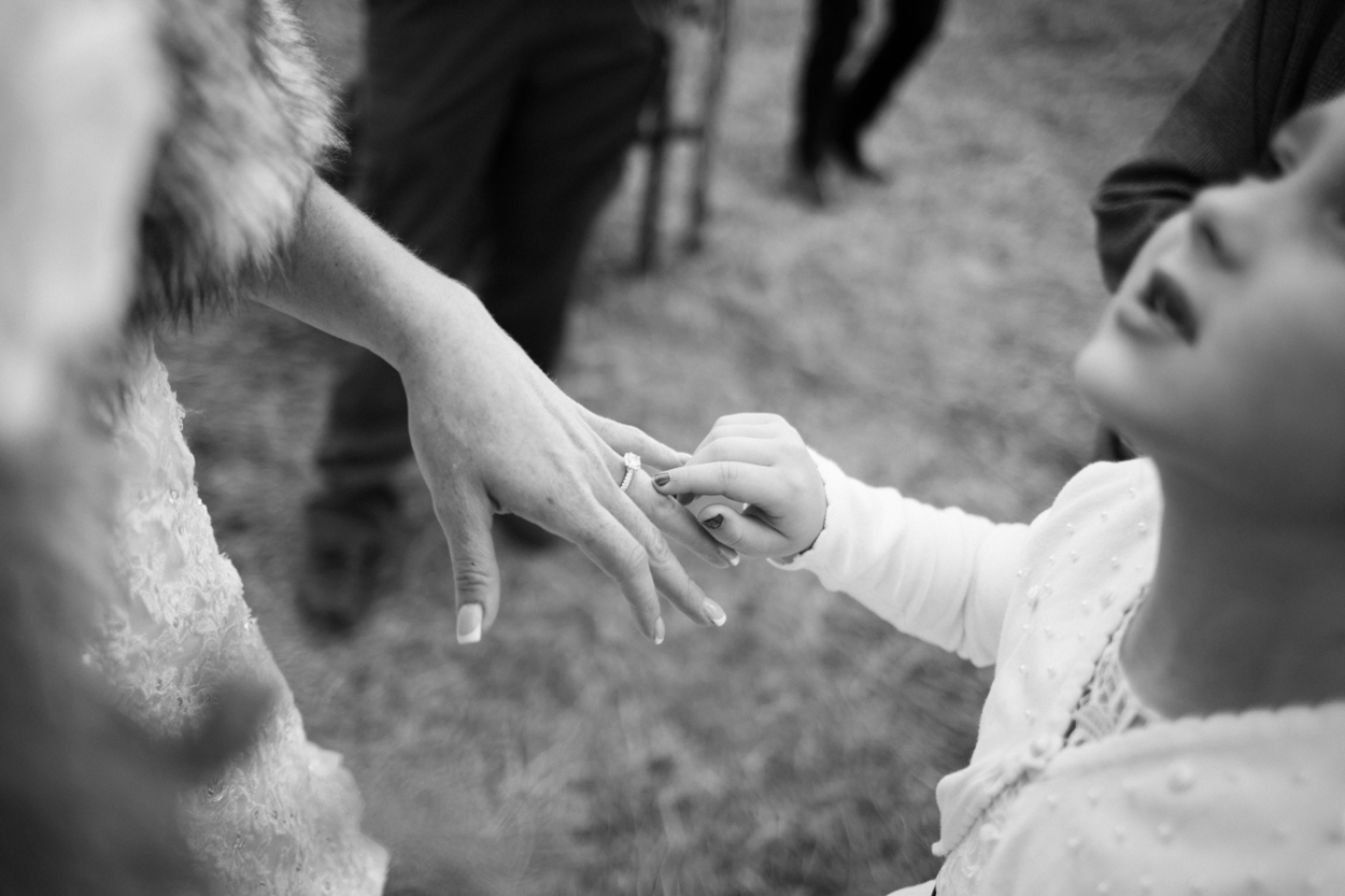 Little girl points at brides wedding ring.