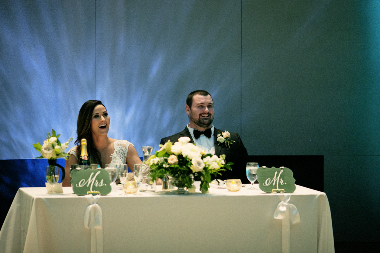 Bride and groom have a laugh during speeches at there wedding reception at the Buffalo Bill Center of the West. Cody wedding photography by Zak Jokela.