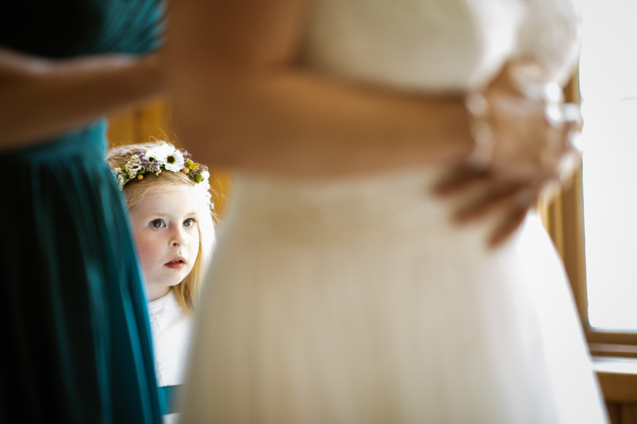 Flower girl looks at bride as she get's ready.