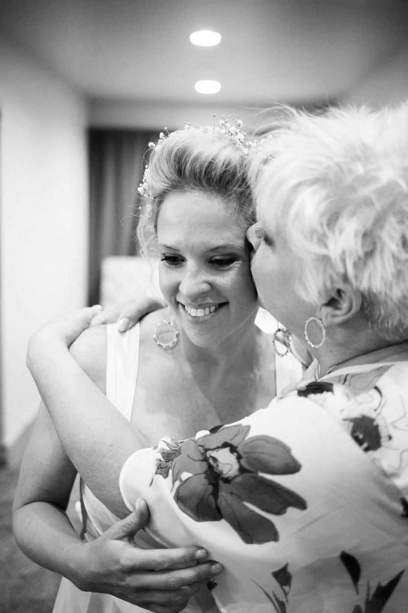 Mom hugs bride on wedding day.