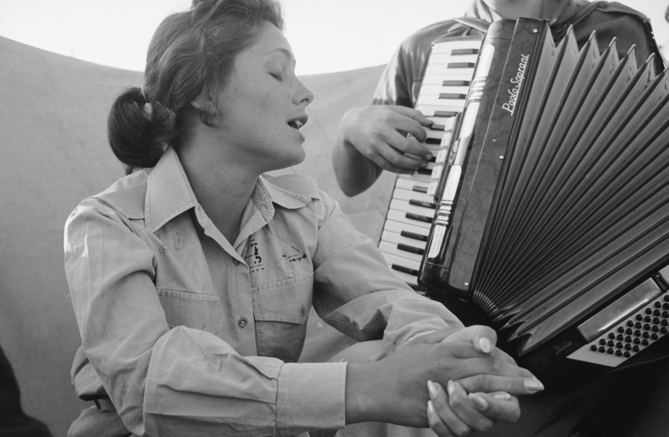 Israeli Woman Soldier Sings While Accompanied by A Soldier Playing an Accordion, Negev, 1960, by Paul Schutzer. Cropped.png