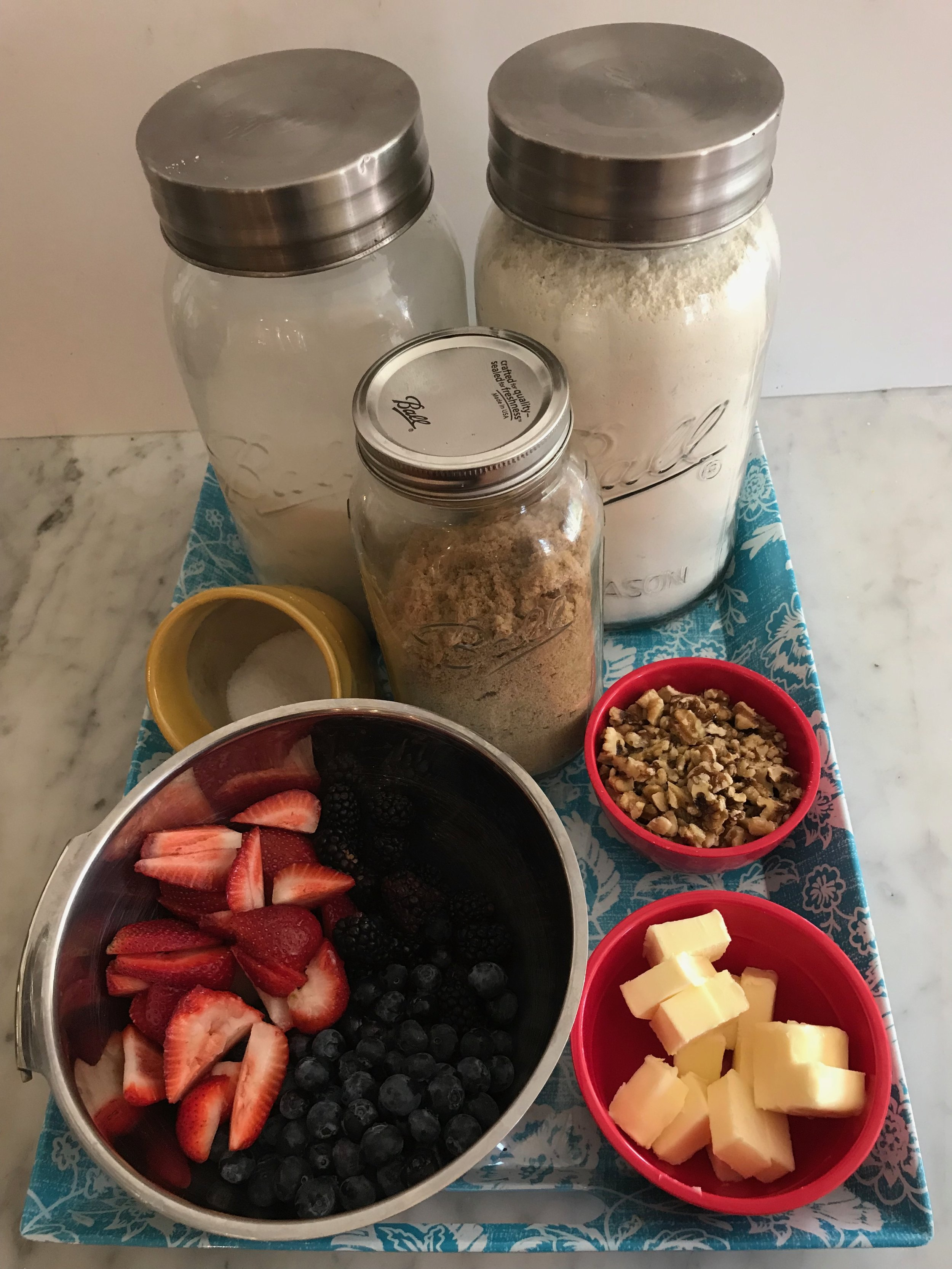 Ingredients - 6 cups berries: blackberries, blueberries, raspberries, or strawberries, washed and cut into pieces½ cup granulated sugarCrumble:1¼ cup all purpose flour2/3 cup golden brown sugarPinch of salt10 tablespoons cold butter, cut into pieces.1½ cups coarsely chopped toasted nuts: walnuts, pecans, or almonds1 pint vanilla ice cream