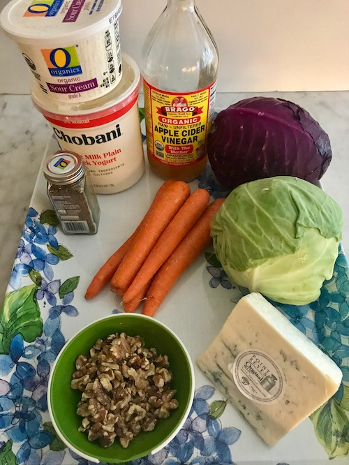 Ingredients - 1 small head of green cabbage1 small head of purple cabbage5 large carrots, peeled¼ cup apple cider vinegar½ cup sour cream½ cup Greek non-flavored yogurt or mayonnaise1 tsp. celery seed.1 tsp. salt1 ½ cup Blue cheese, Roquefort, or Gorgonzola cheese, crumbled½ cup toasted walnuts, chopped