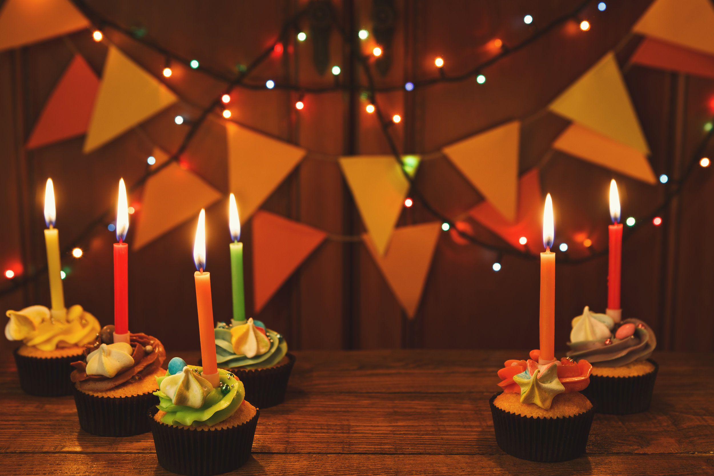 chocolate-cupcakes-with-candles-against-festive-F2TBWSQ.jpg