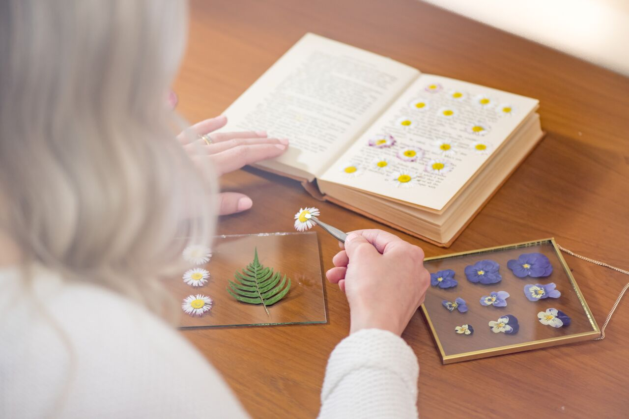 Anna pressing flowers and placing them in her handmade frames