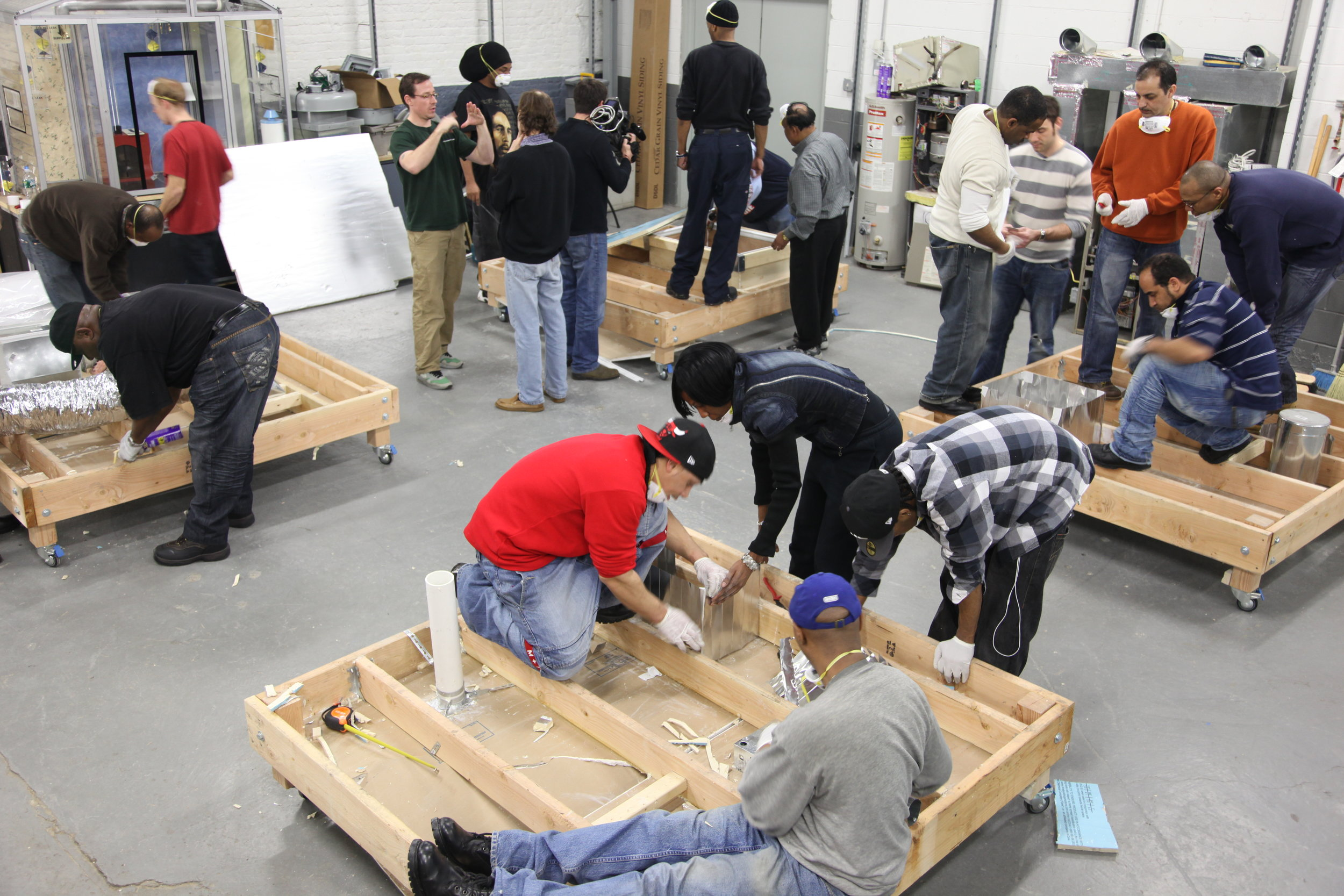 Hands-on lab with attic replicas where trainees practice insulating ducts and pipes.