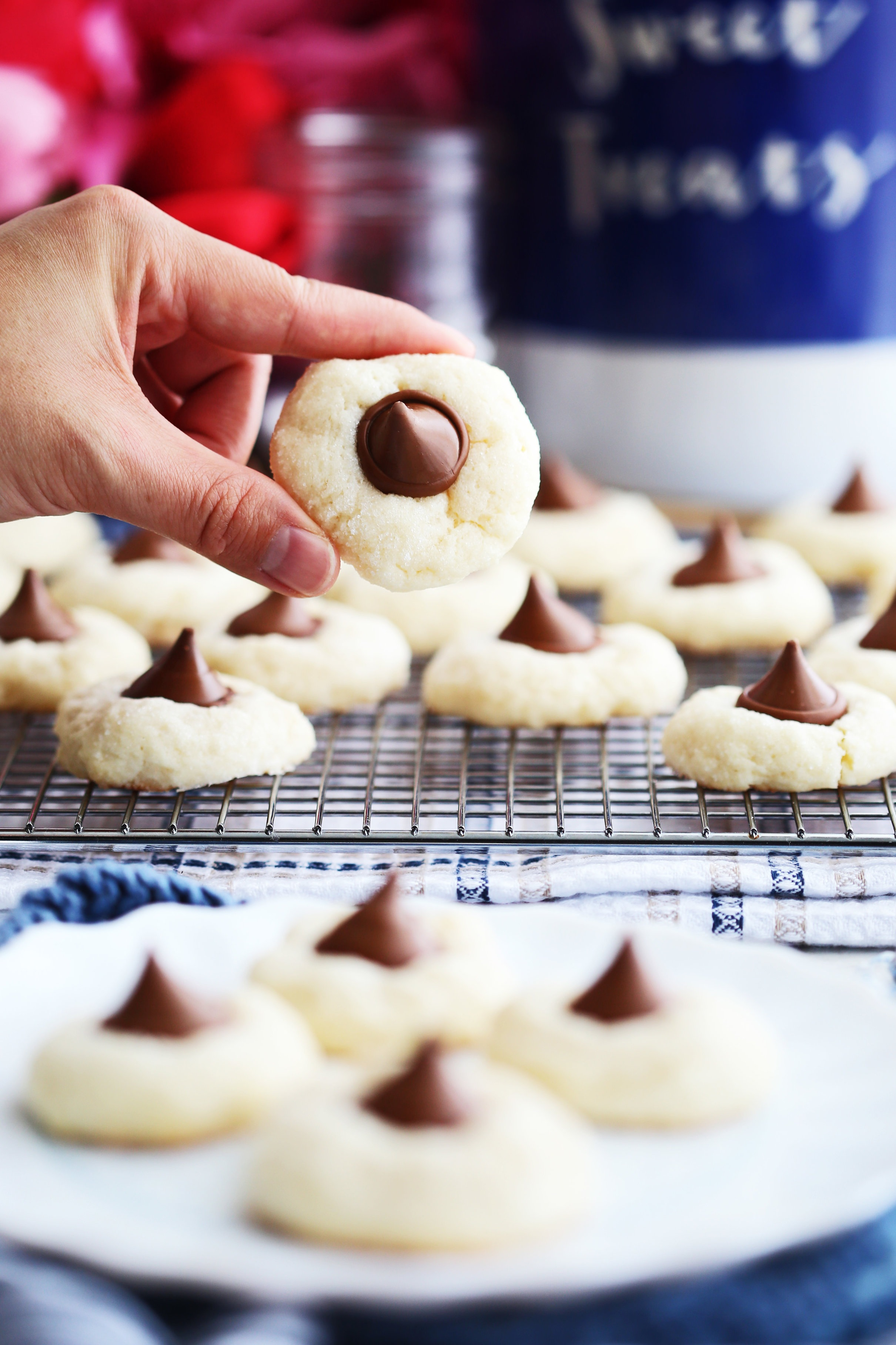 A hand holding up a single Cream Cheese Kiss Cookie over a white plate and cooling rack filled with more Cream Cheese Kiss Cookies.