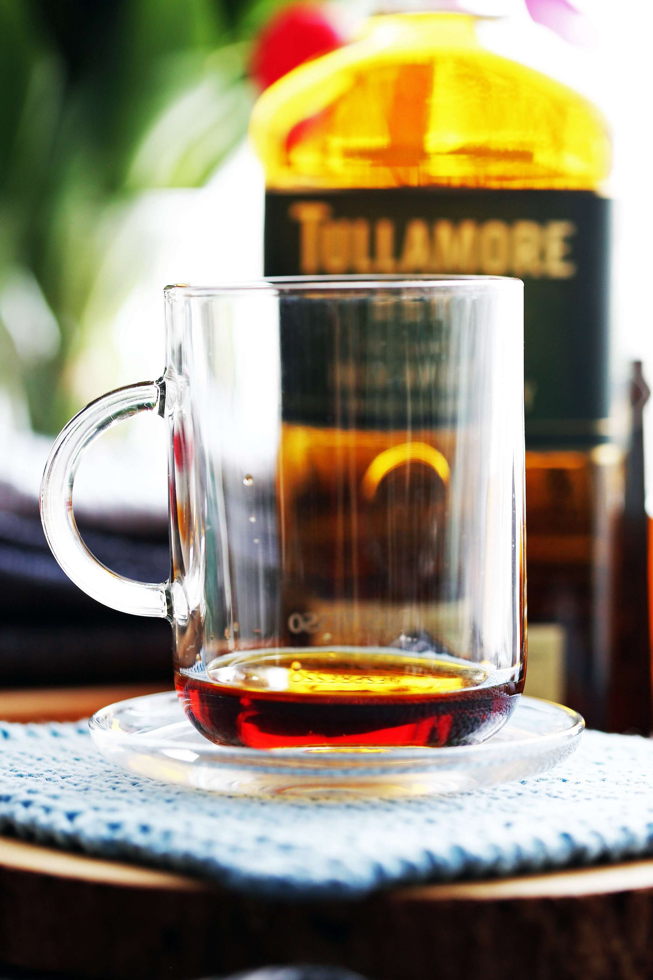 A side view of a glass mug filled with two tablespoons of maple syrup.