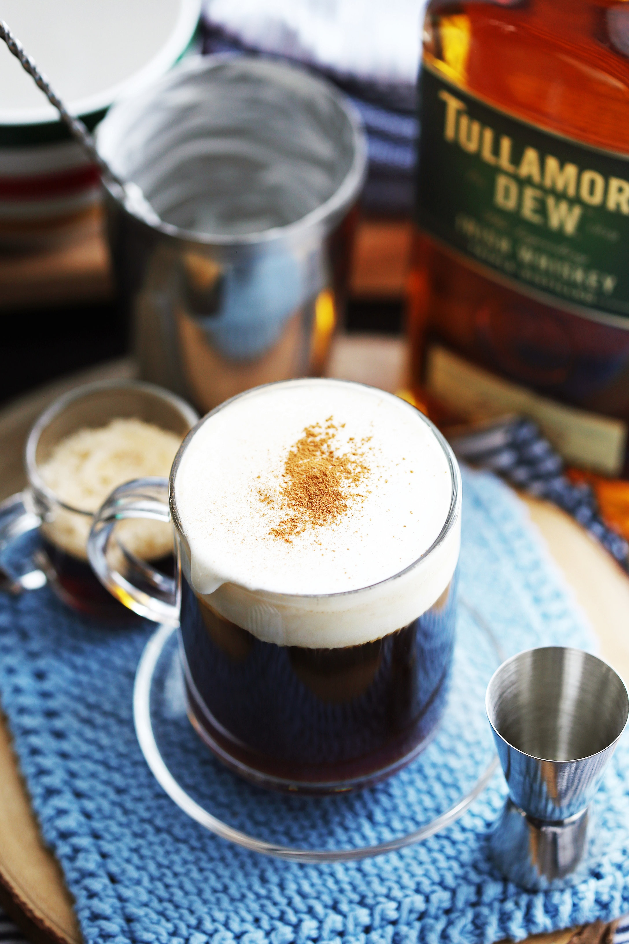 Maple Irish coffee topped with lightly whipped cream and ground cinnamon in a glass mug.