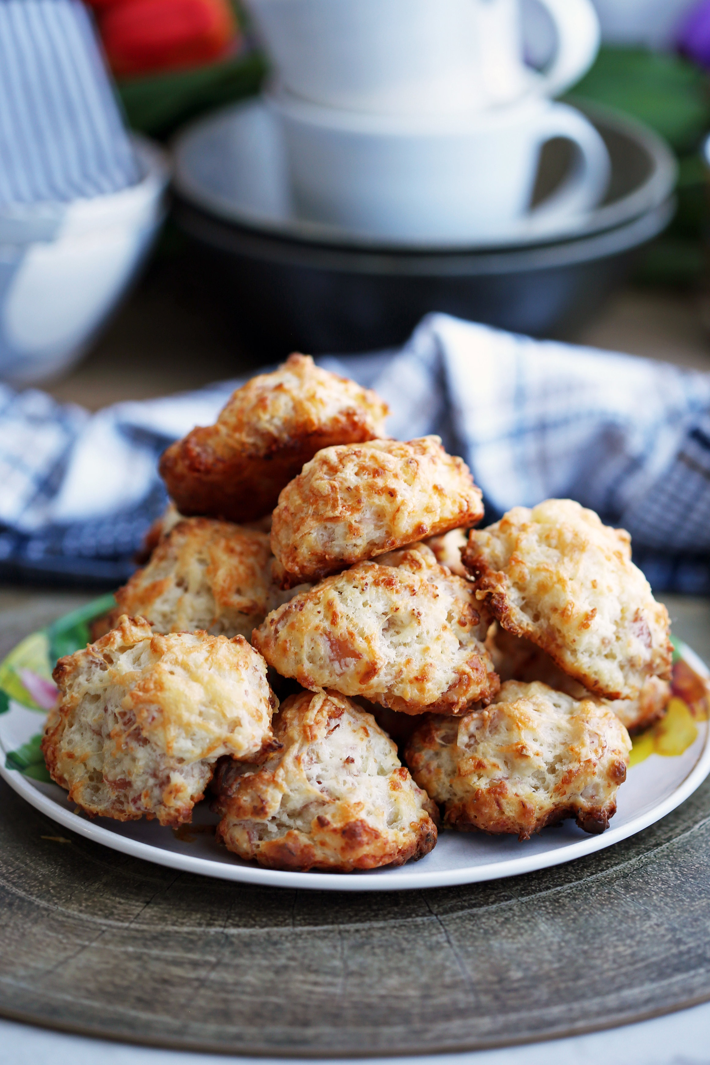 Freshly baked ham and cheese drop biscuits piled on a colourful plate.