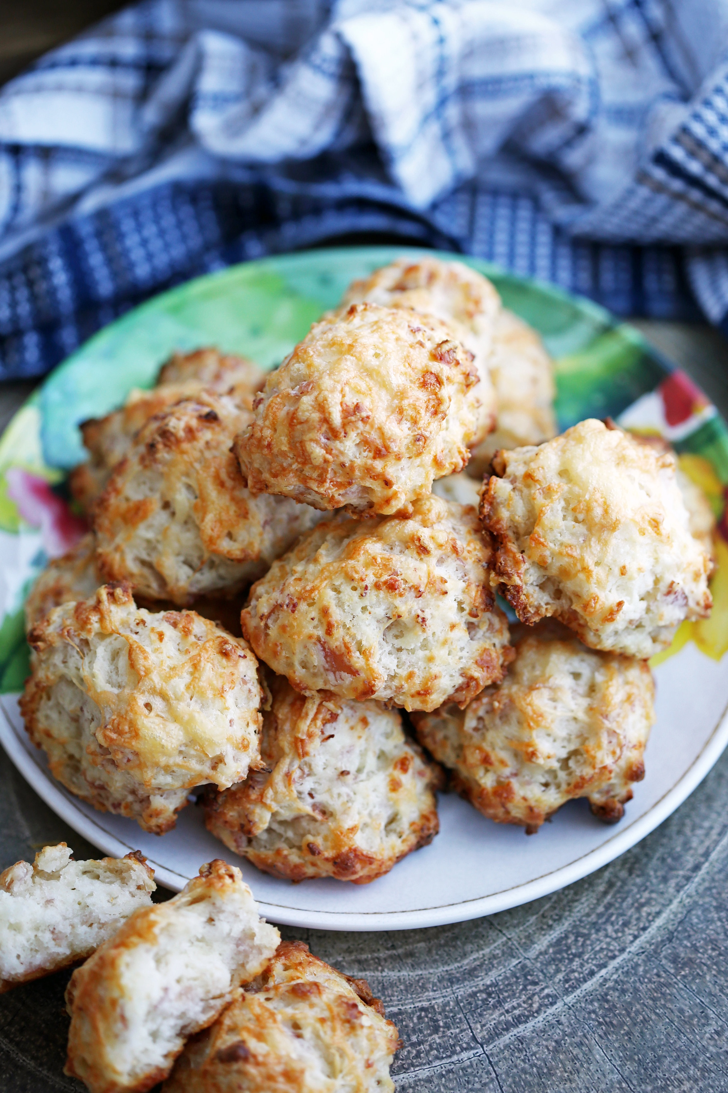 A plate full of freshly baked ham and cheese drop biscuits piled on top of one another.