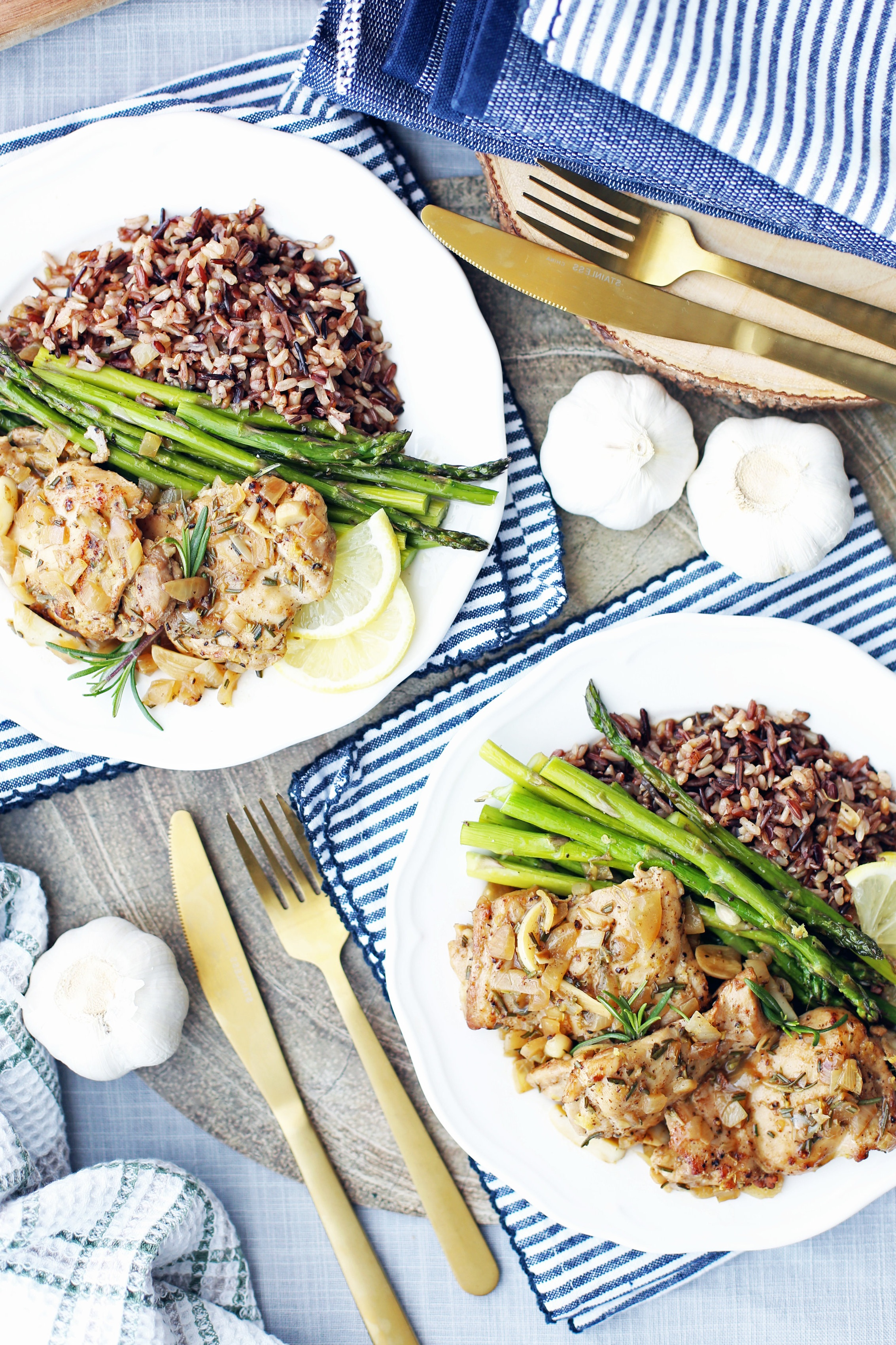Overhead view of two white plates containing rosemary garlic chicken thighs, roasted asparagus, and wild rice.