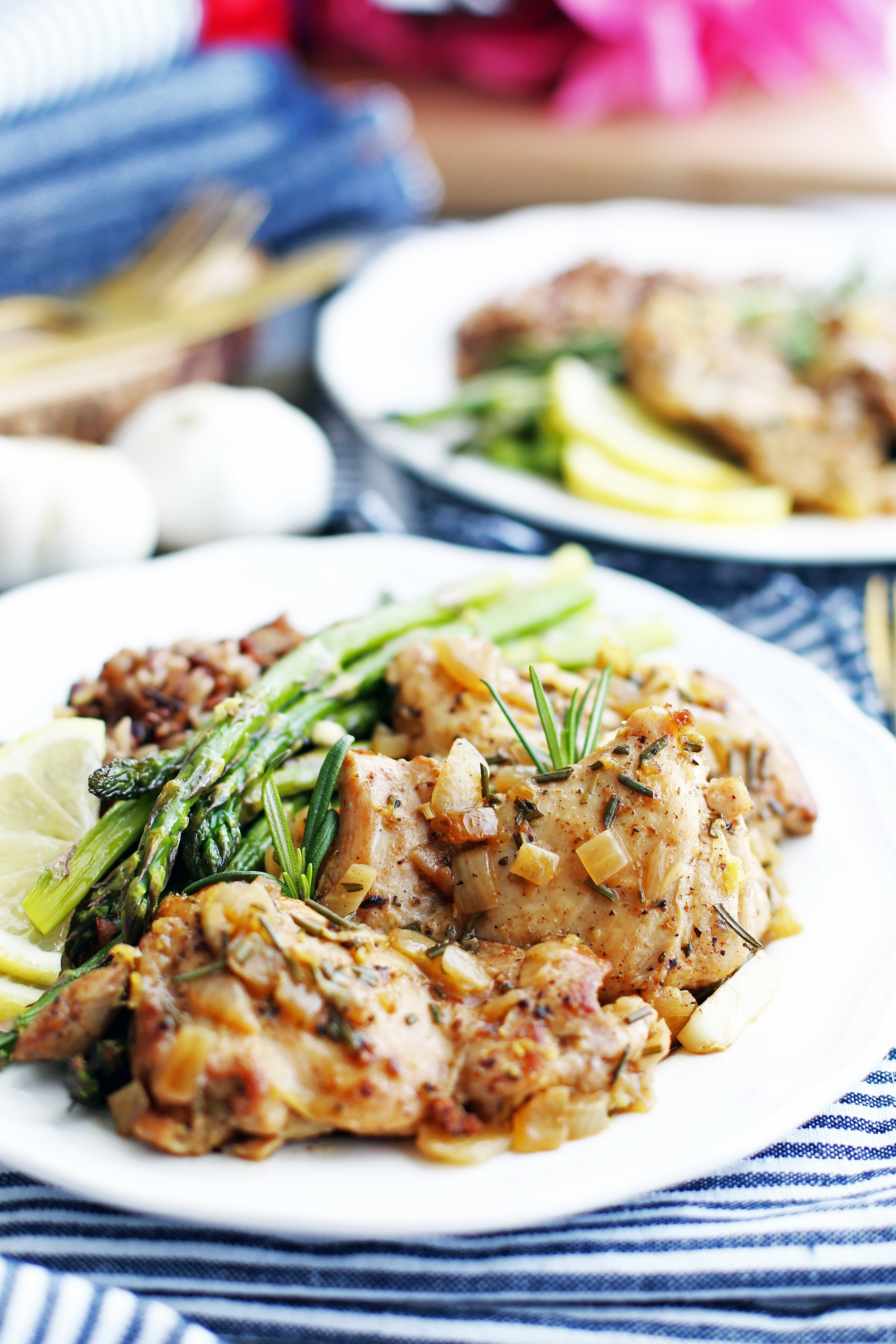 A closeup view of rosemary garlic chicken thighs on a white plate with asparagus and wild rice.