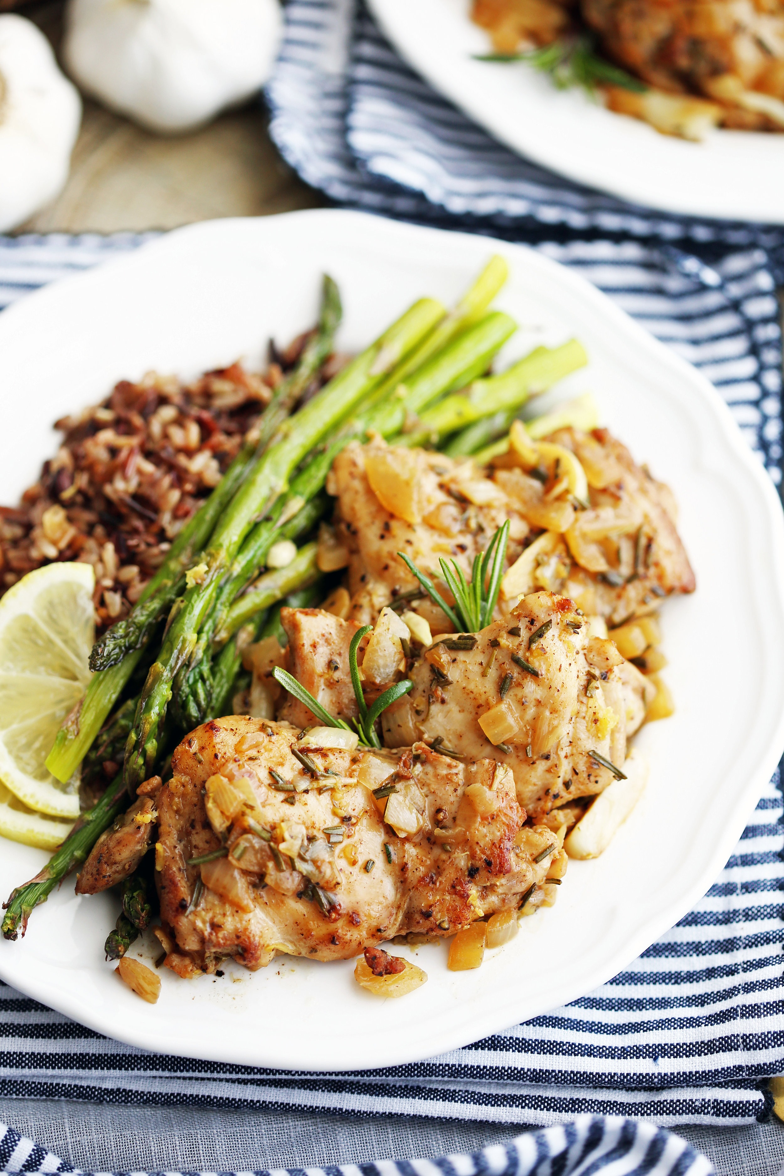 Three rosemary garlic chicken thighs with roasted asparagus and wild rice on a white plate.